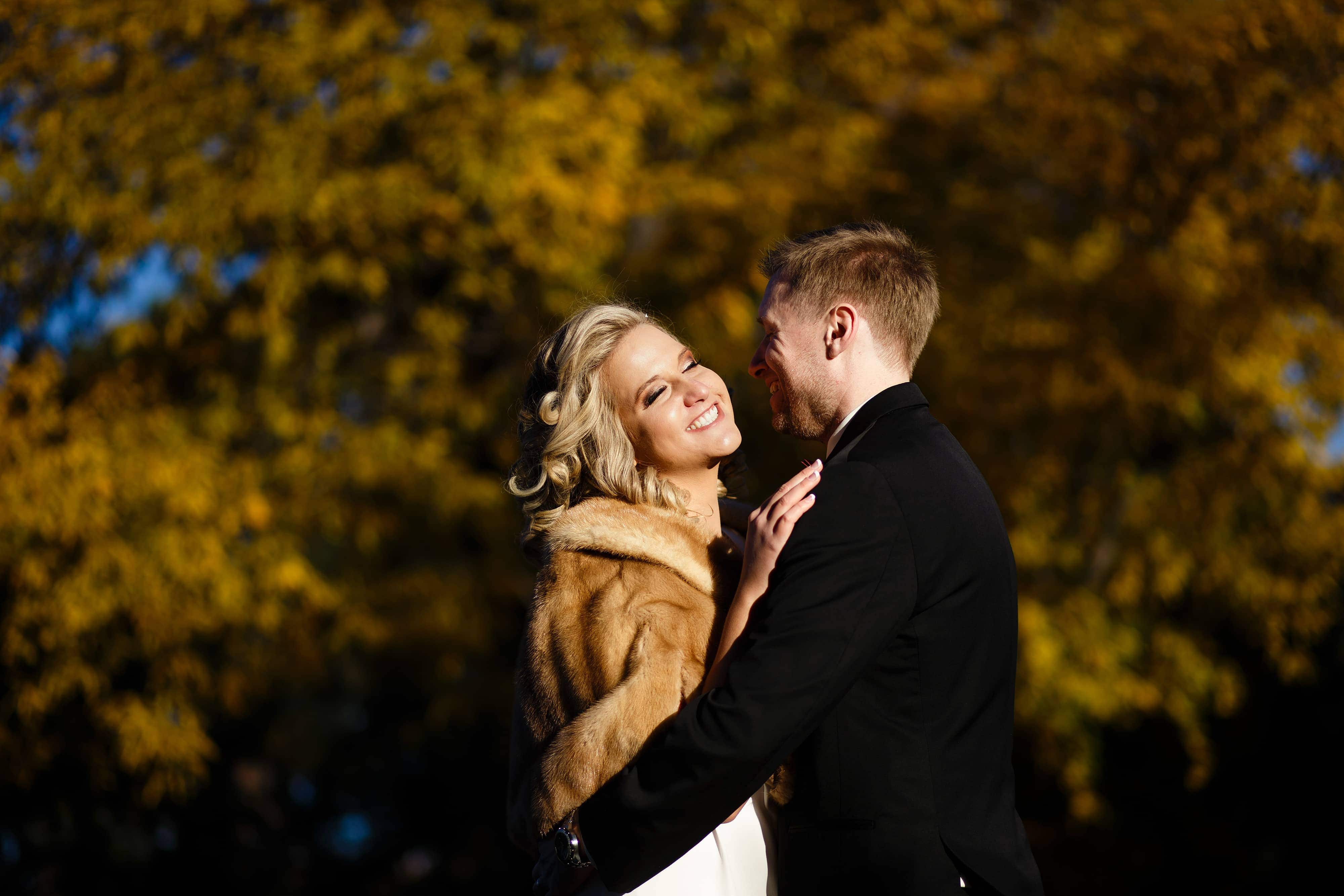Sarah and Ryan share a moment together in front of a golden colored tree at Cheesman Park