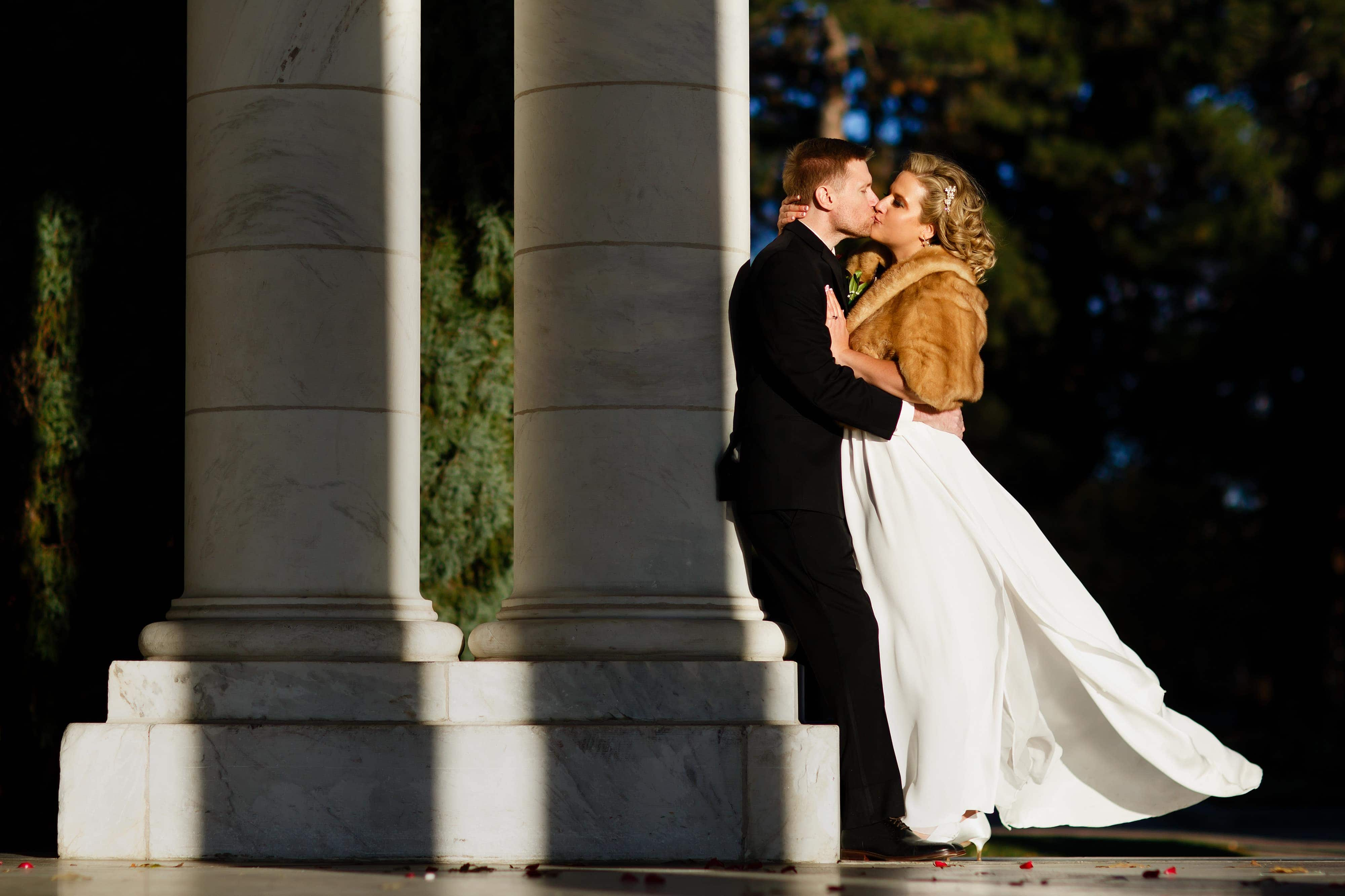 Sarah uses a fur shall to stay warm and embraces Ryan for a kiss in the sunlight after their fall Cheesman Park Wedding