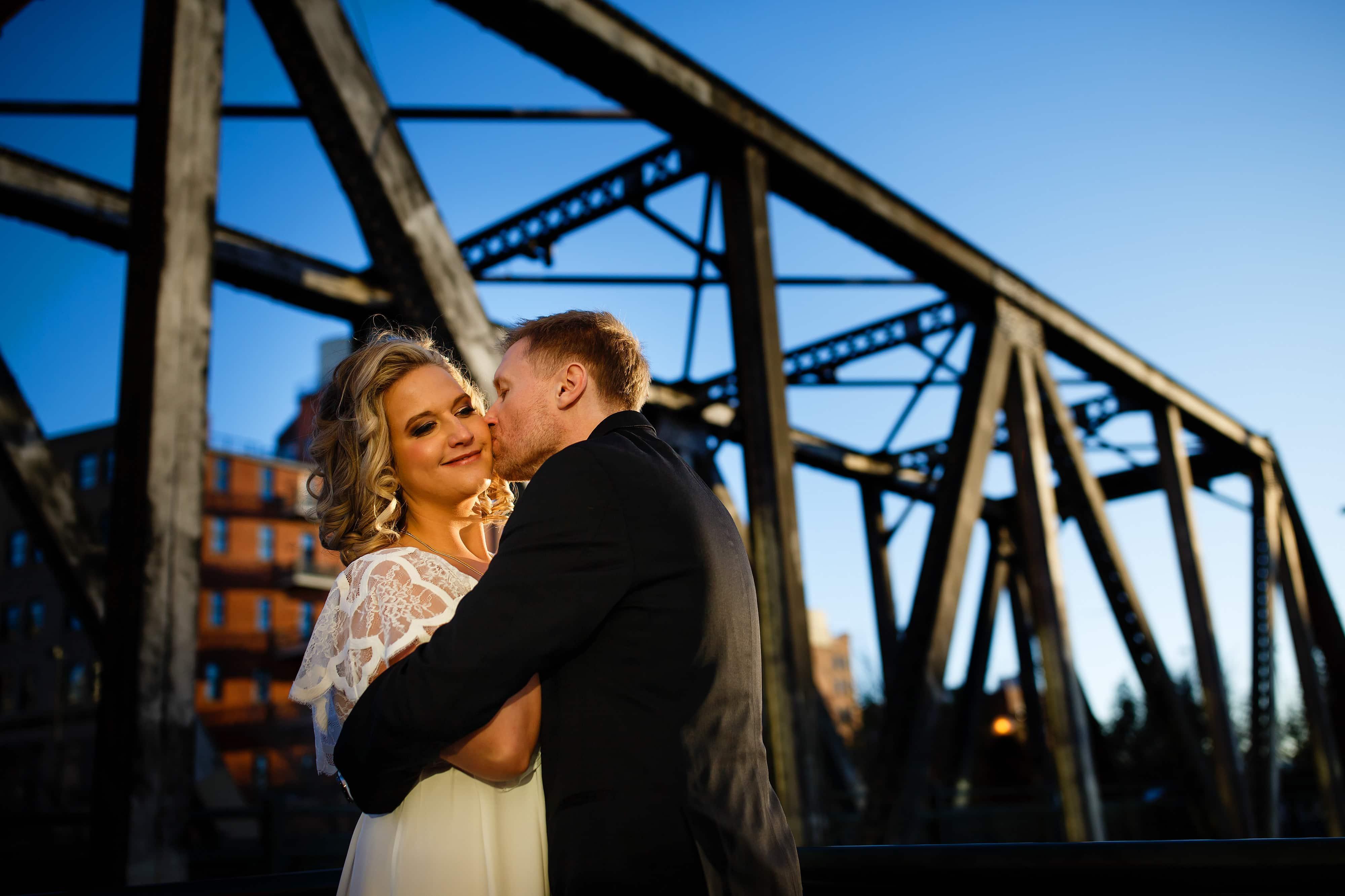 Ryan kisses Sarah on the cheek in front of the Wynkoop Street bridge after their wedding in Denver