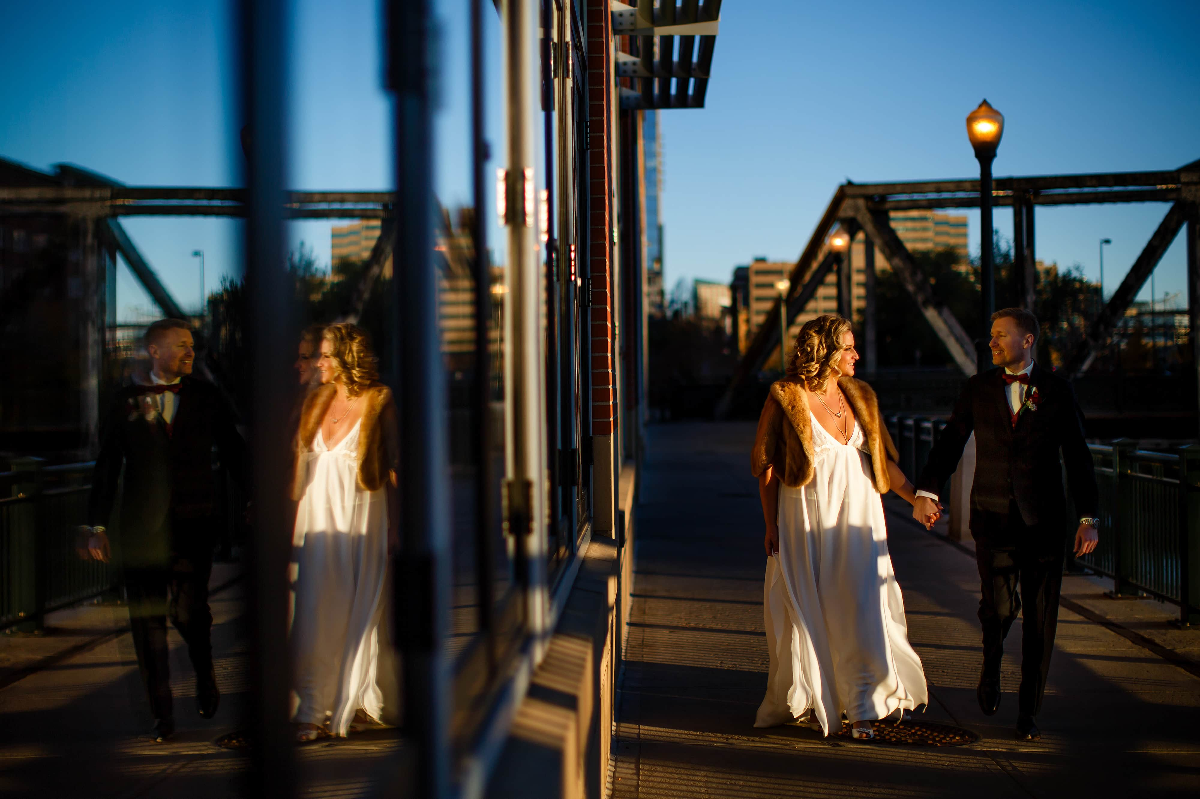 The couple is reflected in a building while walking togher in LoDo after their wedding