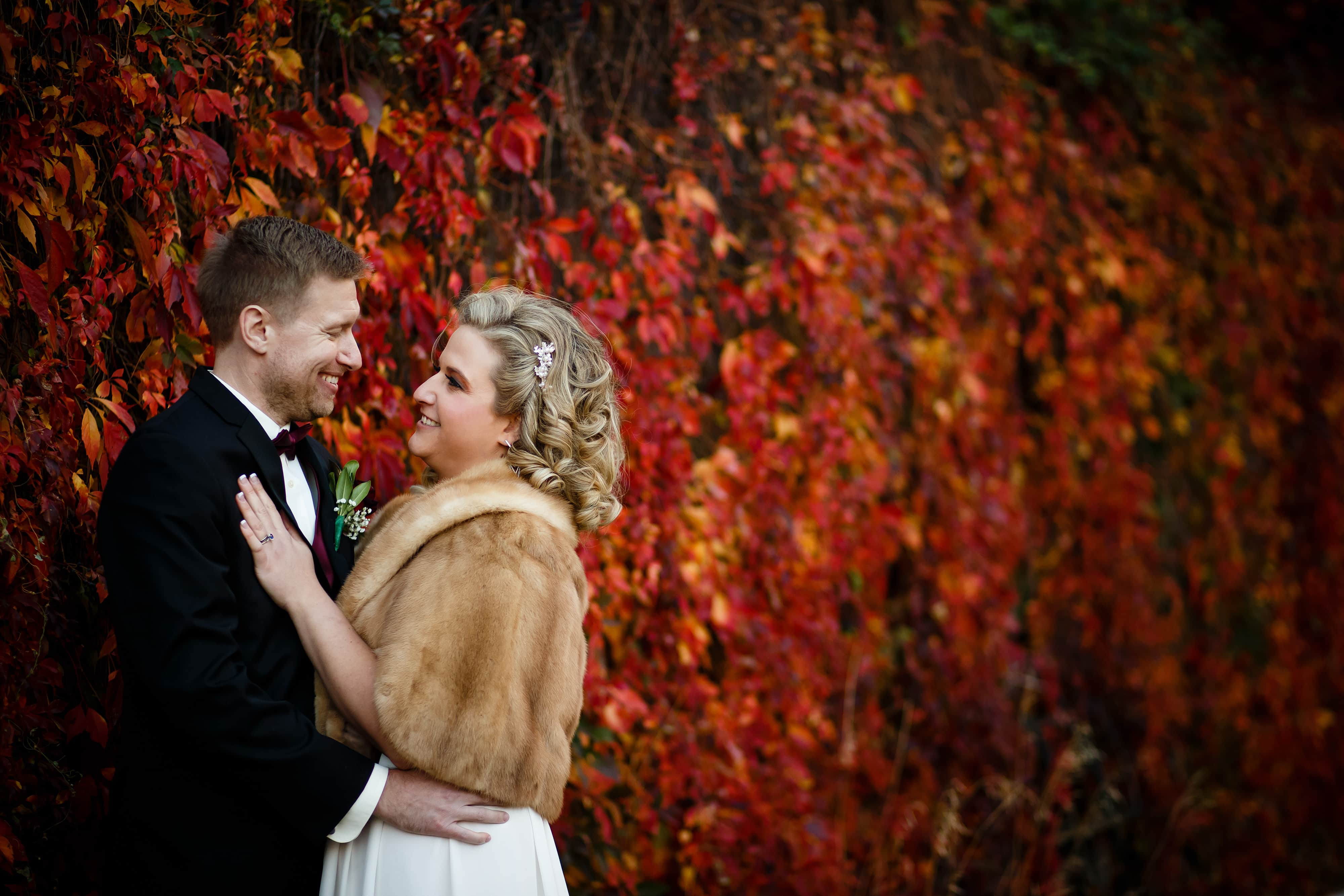 Sarah and Ryan share a moment together in front of a red colored ivy wall near the Cherry Creek path on their wedding day