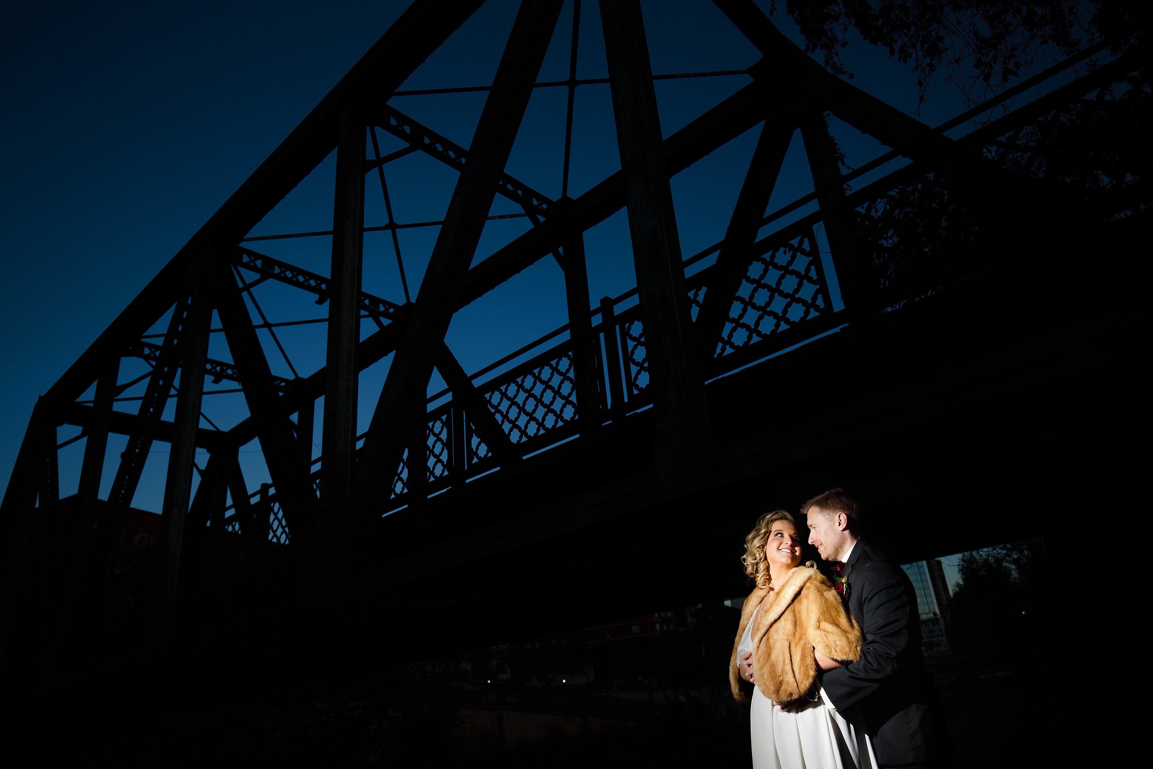 The couple is illuminated under the Wynkoop Street bridge during twilight after their fall wedding in Denver