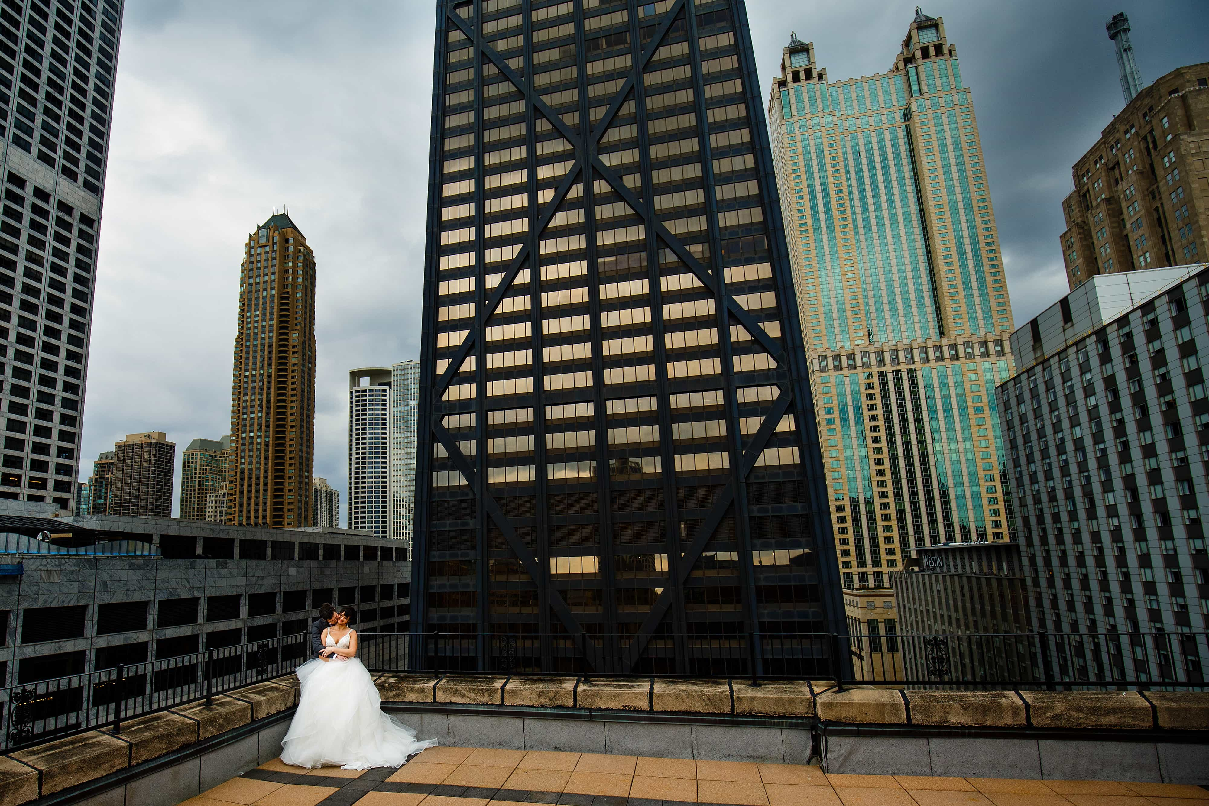 Chelsea and Ori embrace on a rooftop in downtown Chicago near the Hancock building