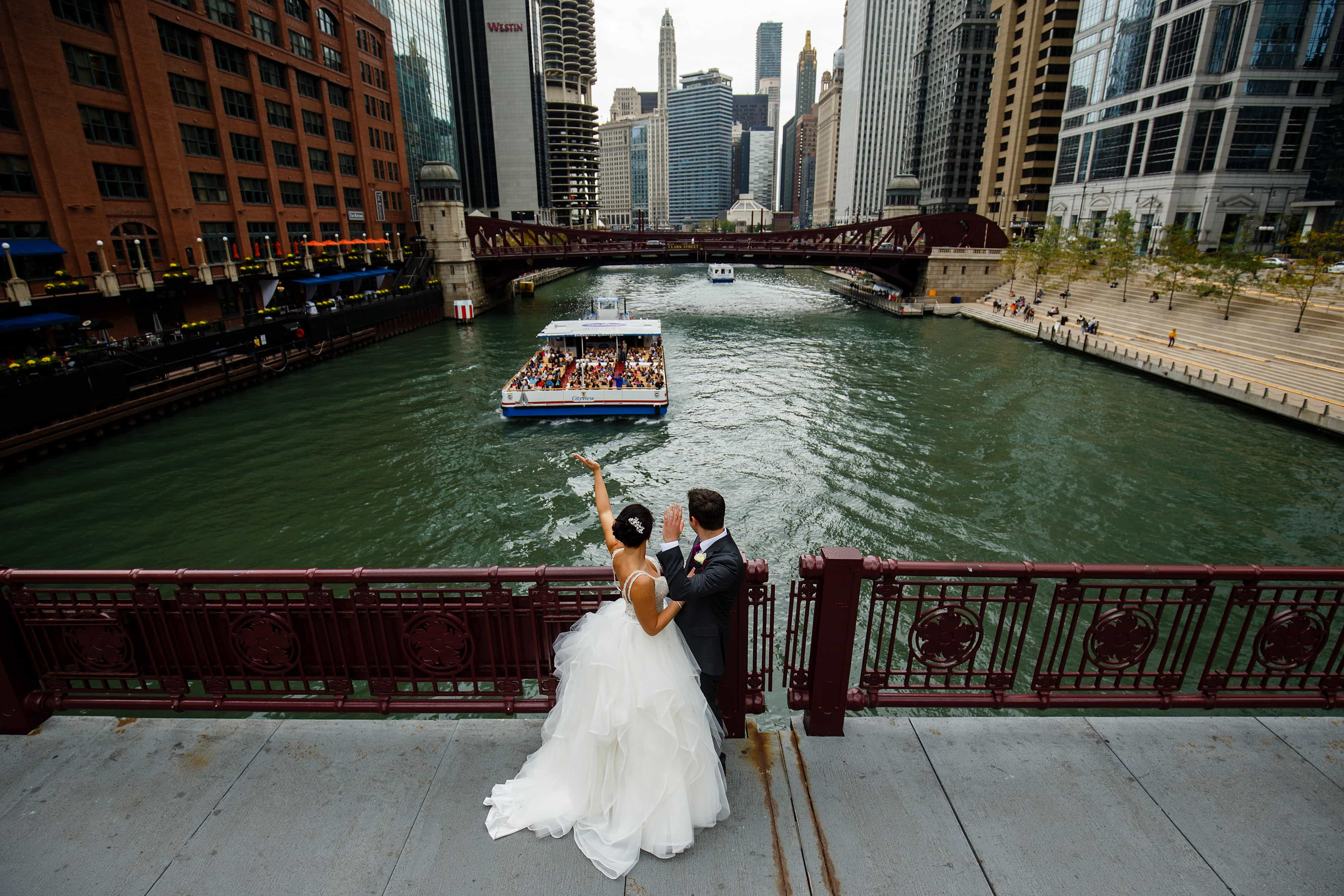 The bride and groom wave to tourists on a boat on the Chicago River during their fall wedding