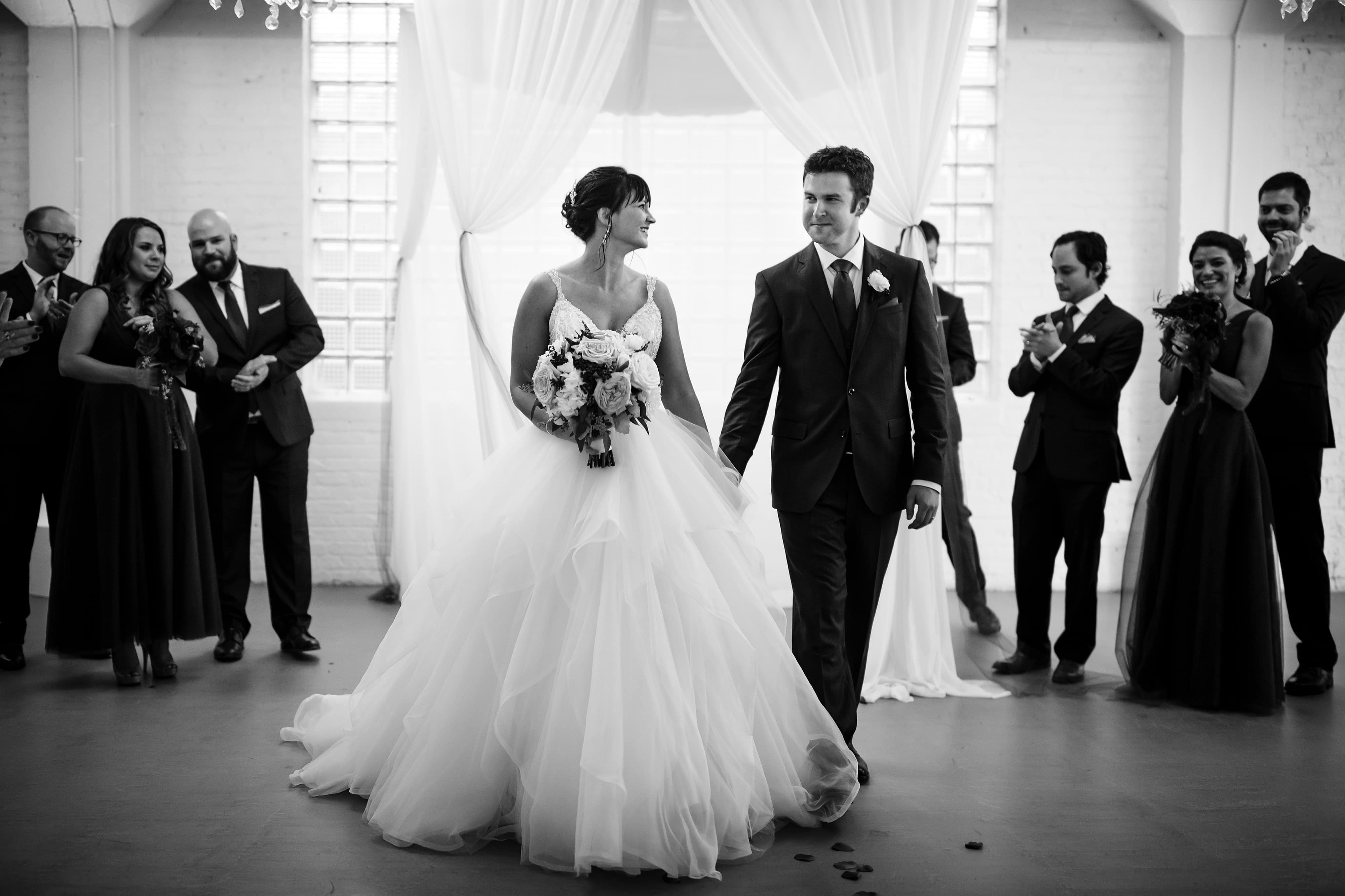 Chelsea and Ori walk down the aisle together after being married at Room 1520