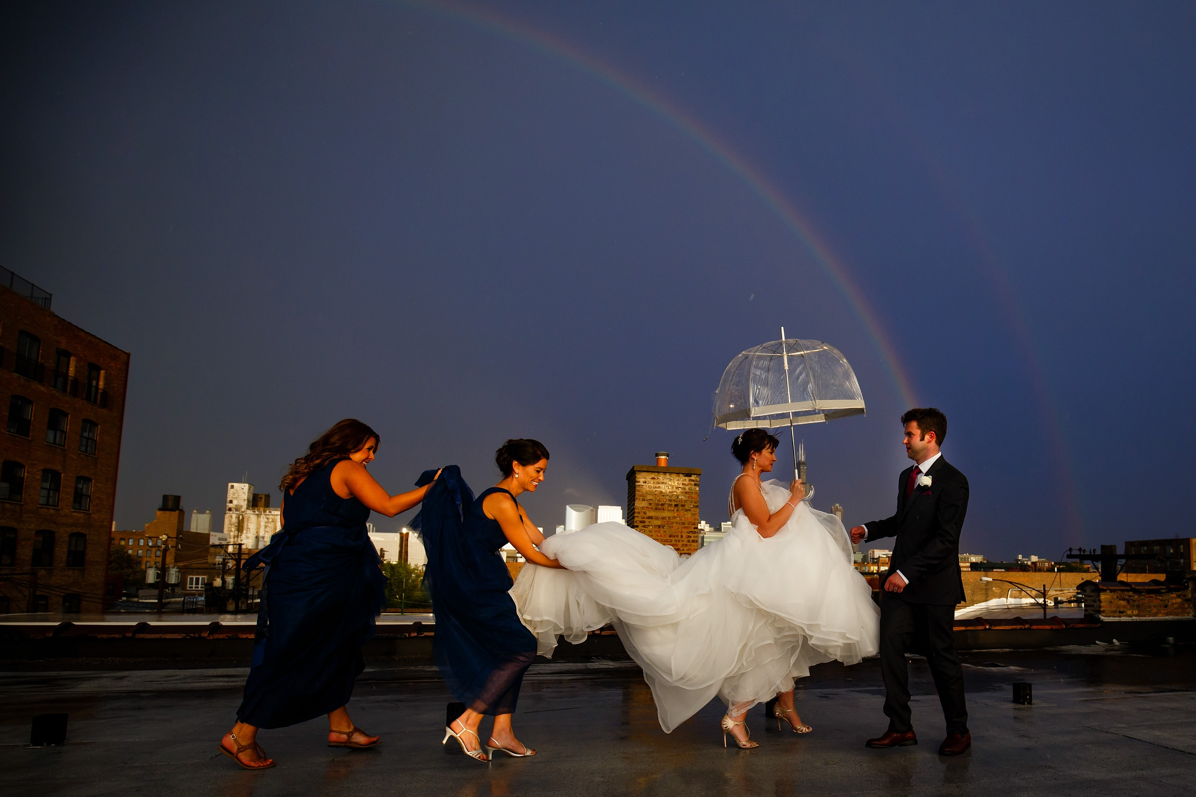 Chelsea gets some help with her dress on the rooftop above Room 1520 as rain falls and a rainbow is emerges in the sky