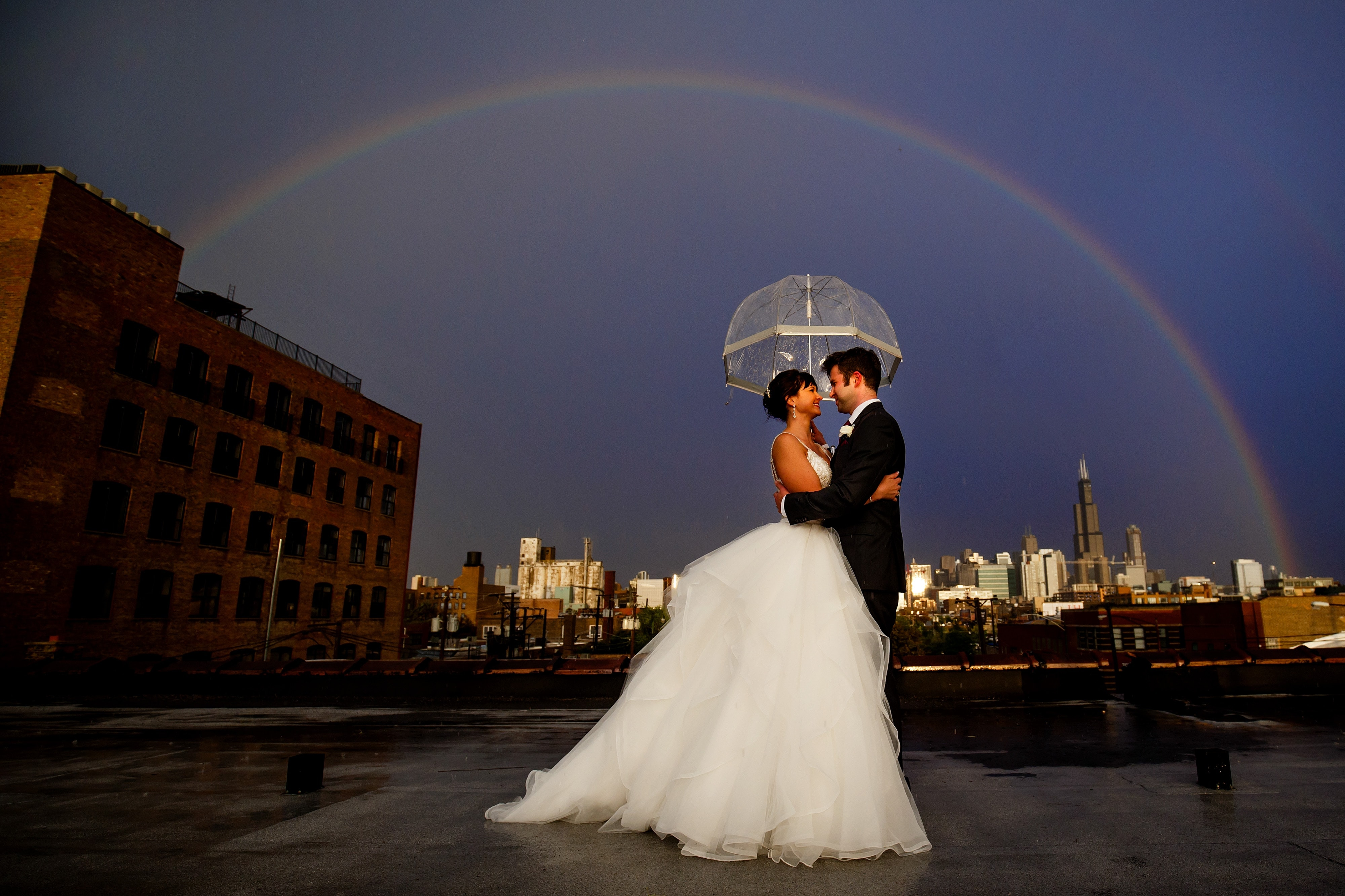 Chelsea and Ori embrace under an umbrella as they're surrounded by a rainbow on the rooftop during their Room 1520 wedding in Chicago