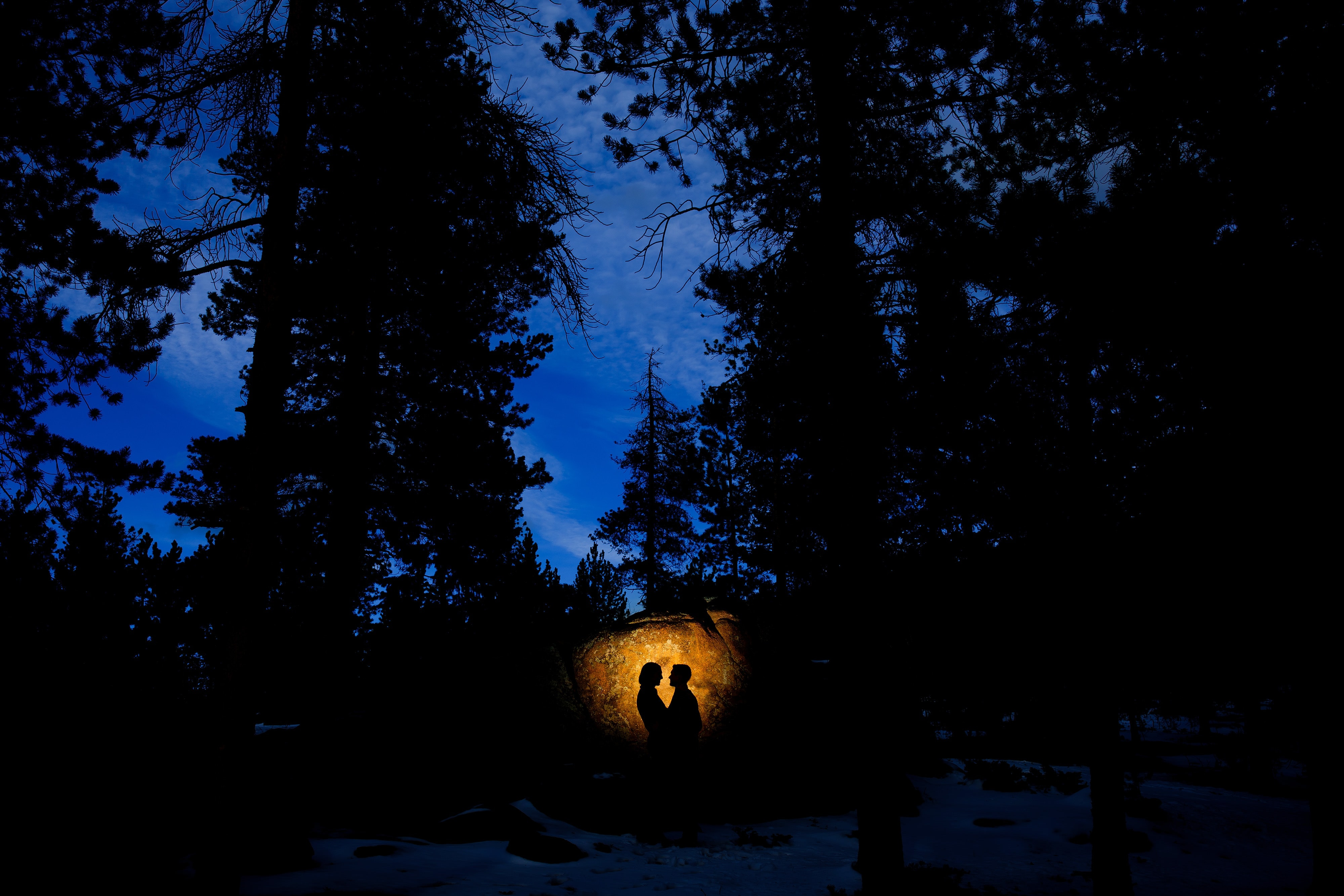 A couple are silhouetted against a rock in Evergreen during their creative engagement photo session