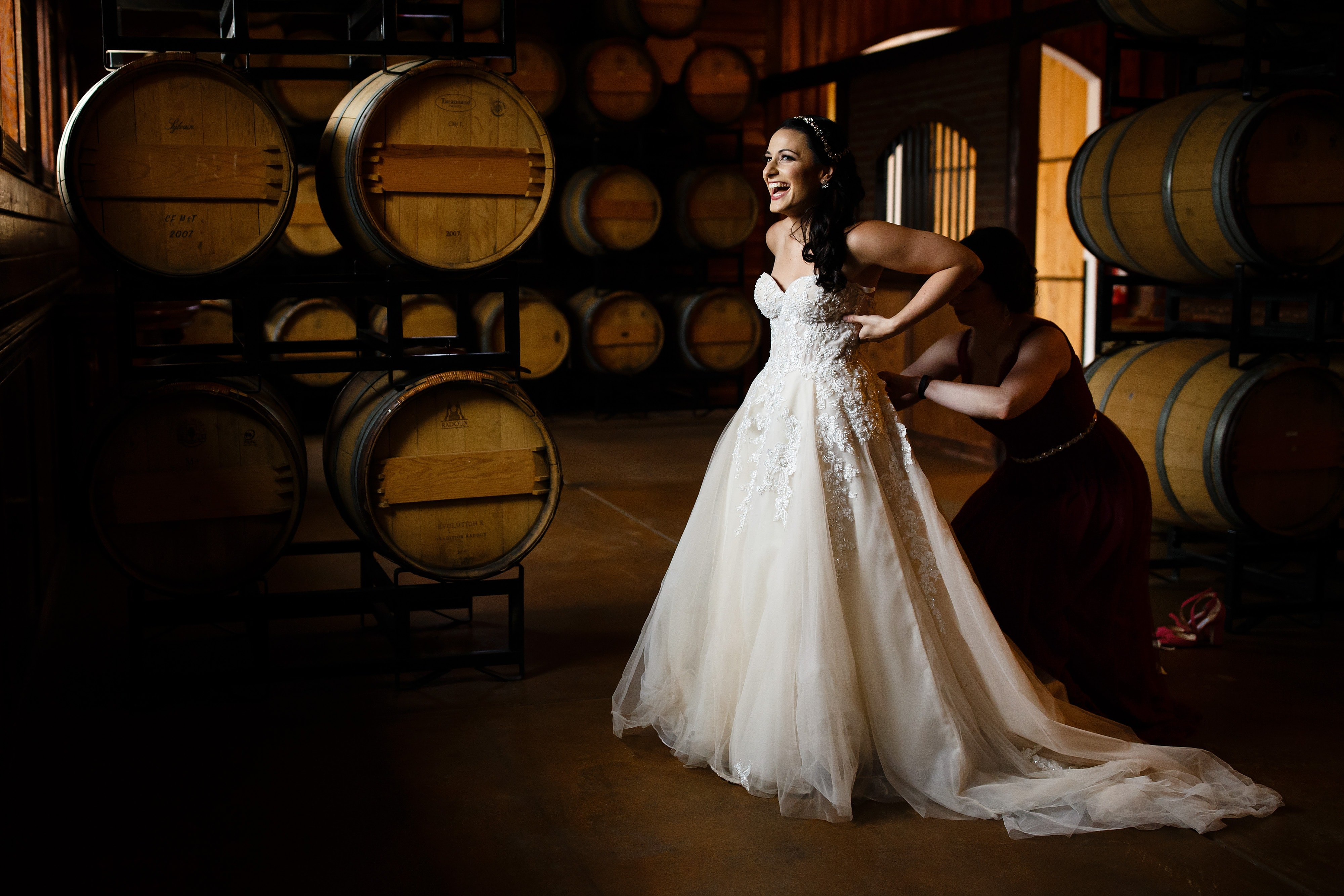 Danielle laughs while putting on her dress in the barrell room before her Crooked Willow Farms wedding in Larkspur, Colorado