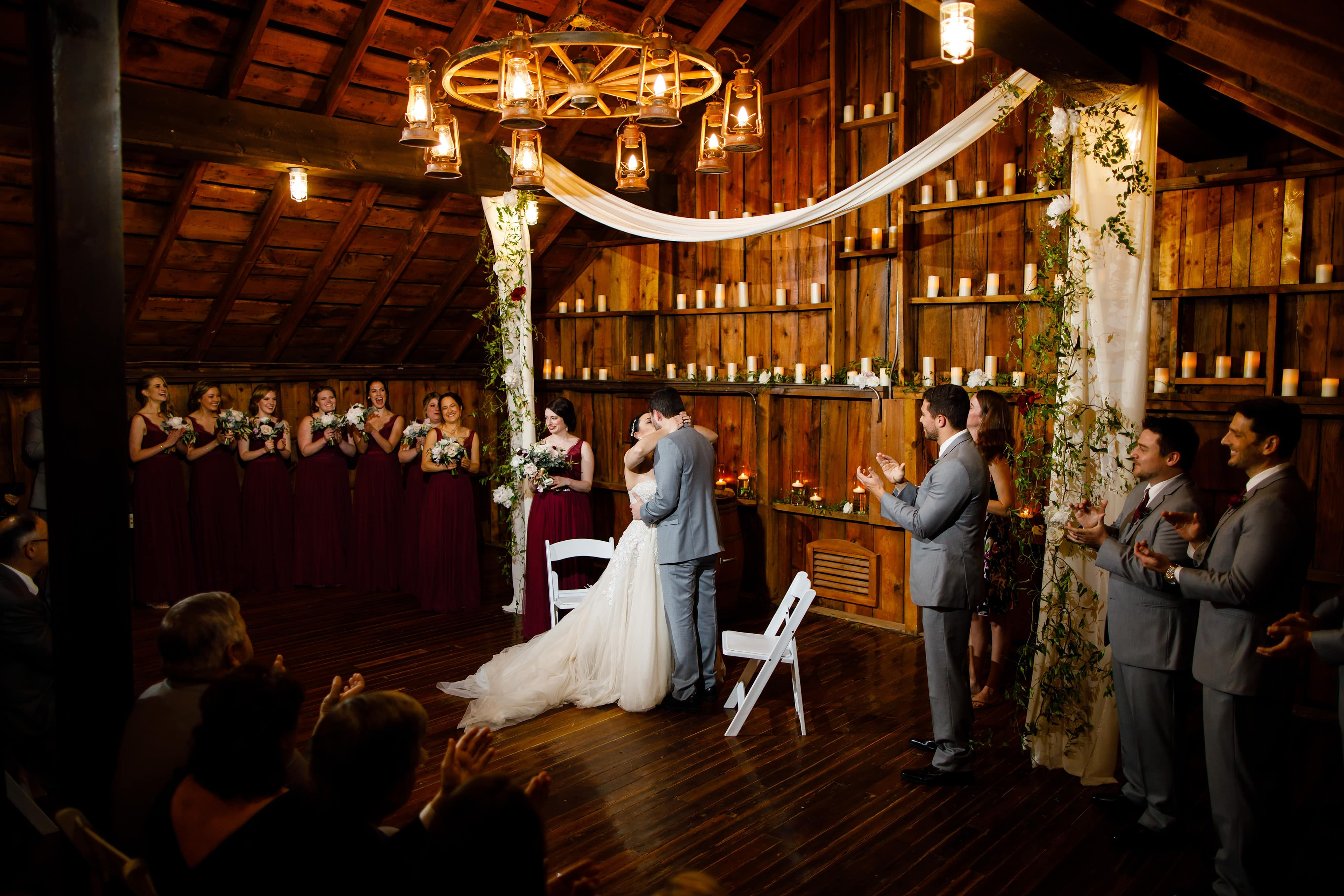 The couple shares their first kiss in the rustic barn loft space during their Crooked WIllow Farms Wedding in Larkspur, Colorado