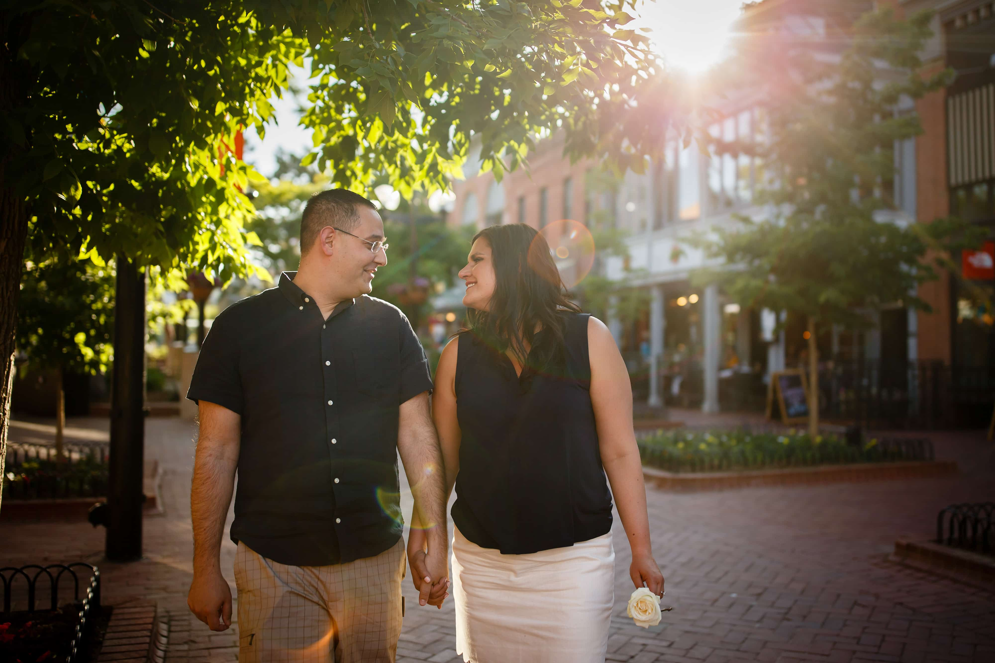 Dimitra and George walk together during their engagement photos in Boulder Colorado on Pearl Street