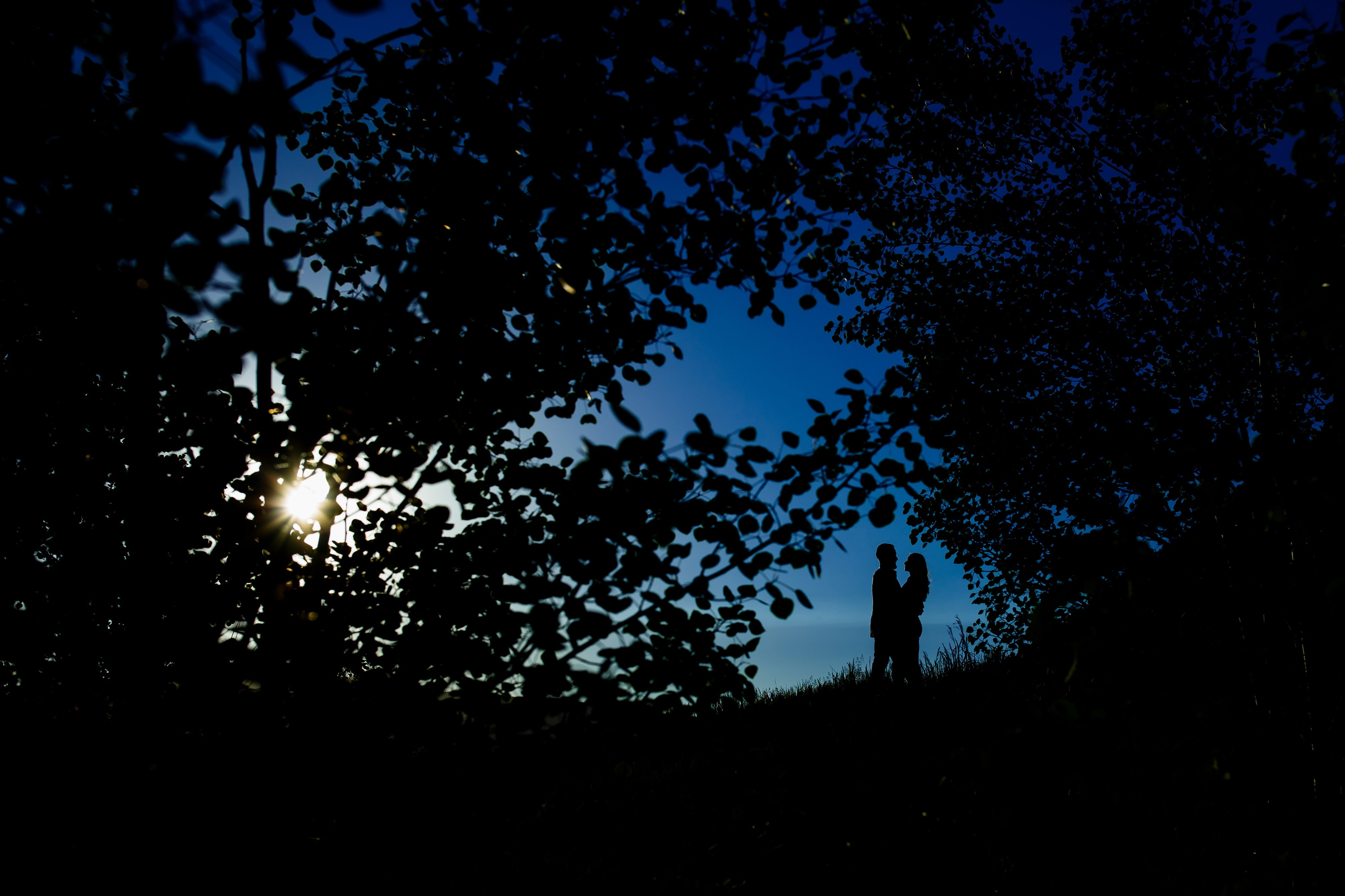 Sharon and Nick are silhouetted against the blue sky during their colorful engagement in Golden Gate Canyon State Park