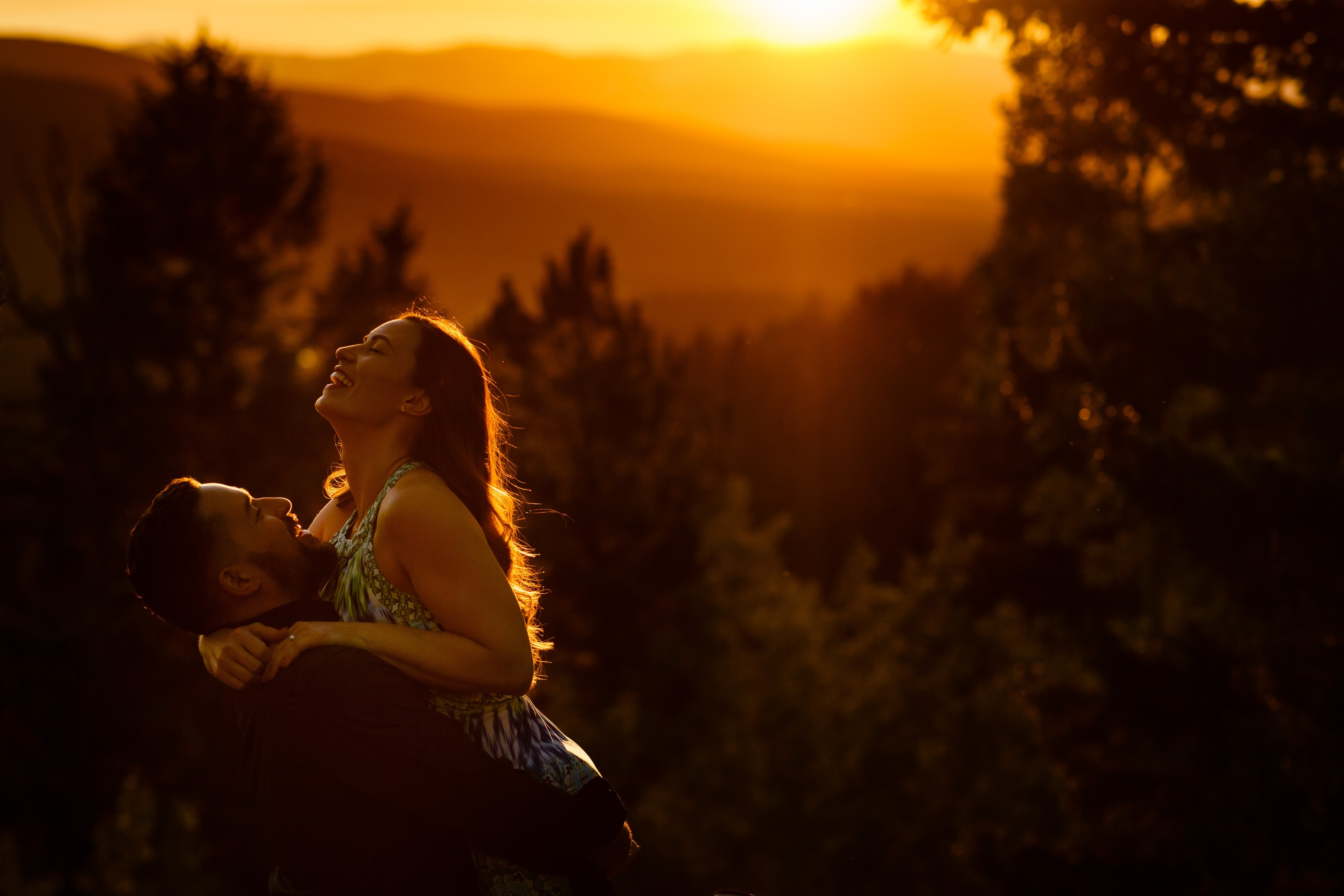 Nick picks up Sharon as the sun sets during their colorful engagement in Golden Gate Canyon State Park