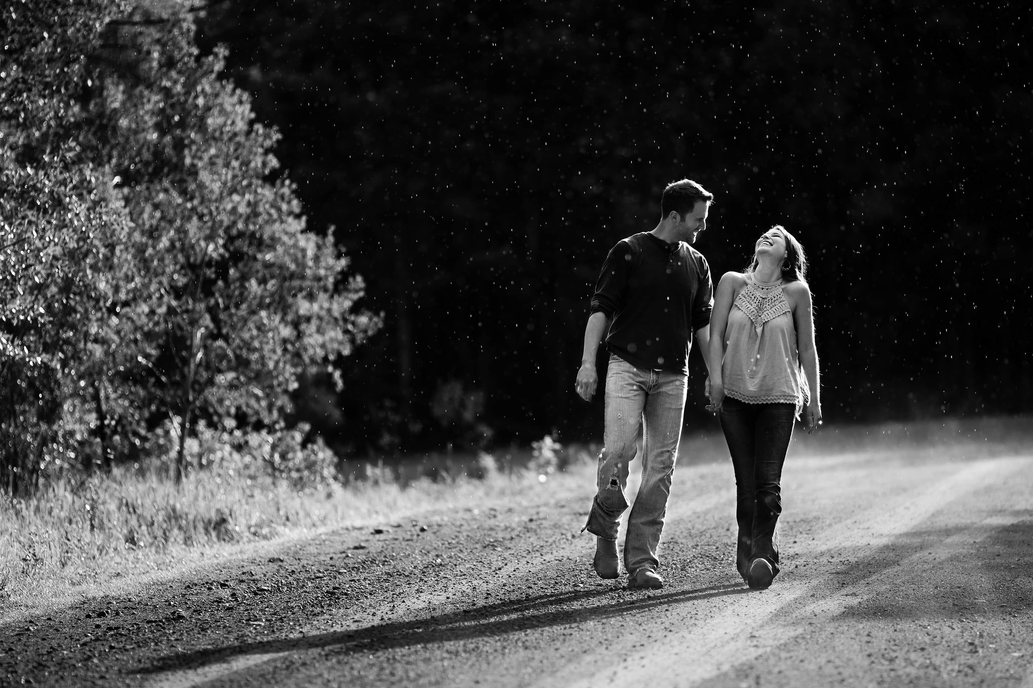 A couple walk in the rain during their engagement session at Meadow Creek Trailhead in Frisco