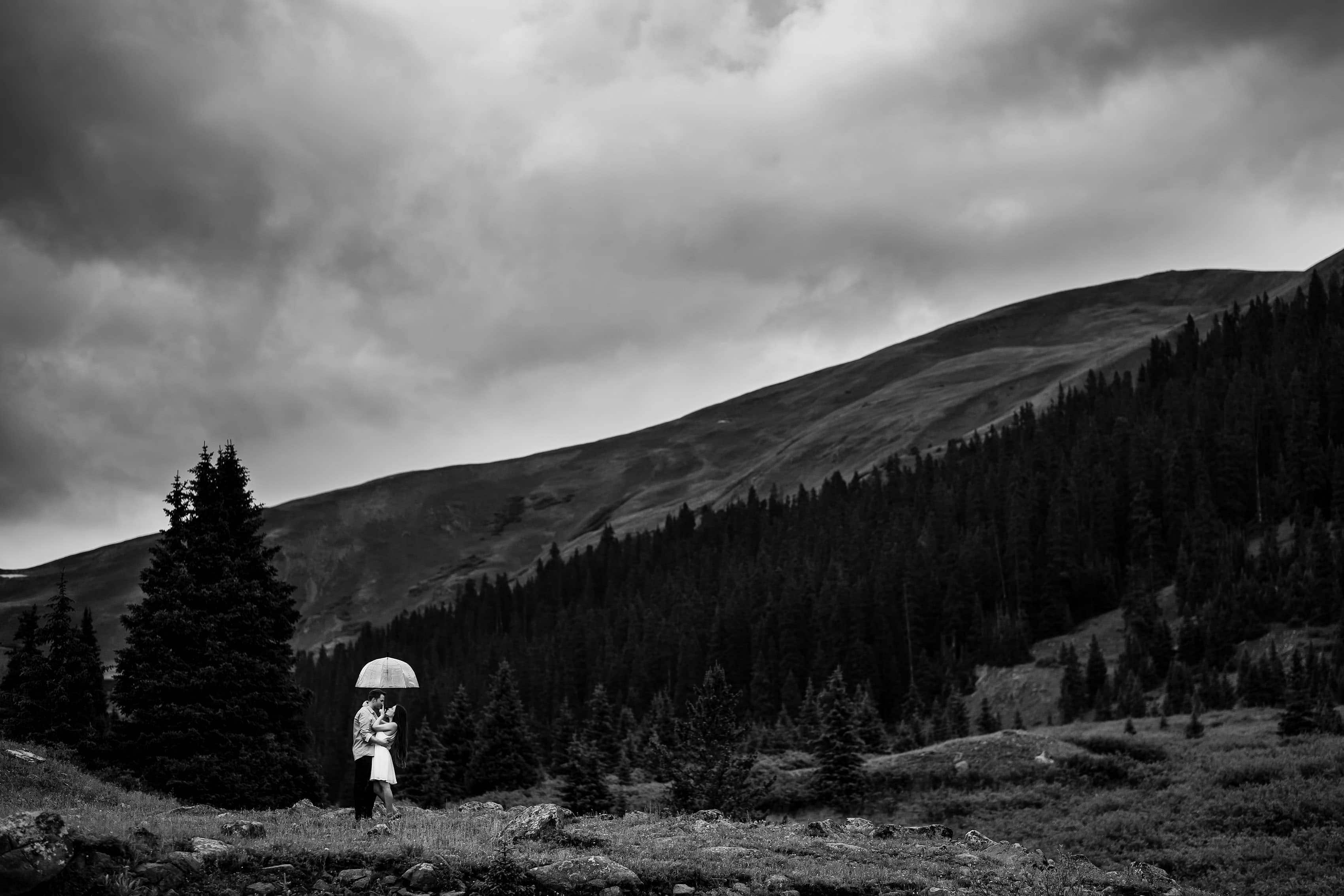 Aaron and Alesha stay dry under an umbrella while posing on Loveland Pass