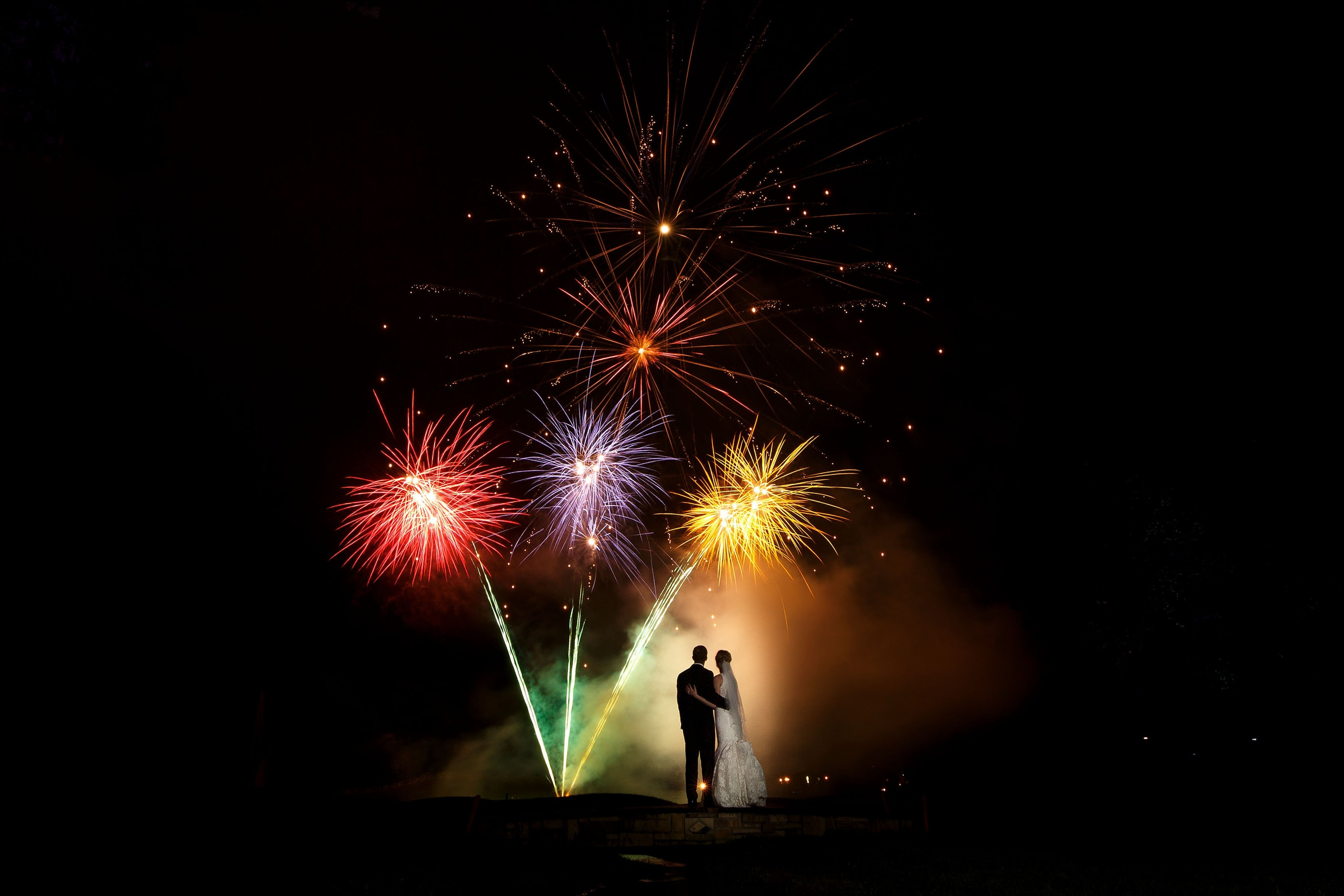 A bride and groom are illuminated by fireworks at a Trappers Turn Golf Course wedding in Wisconsin Dells