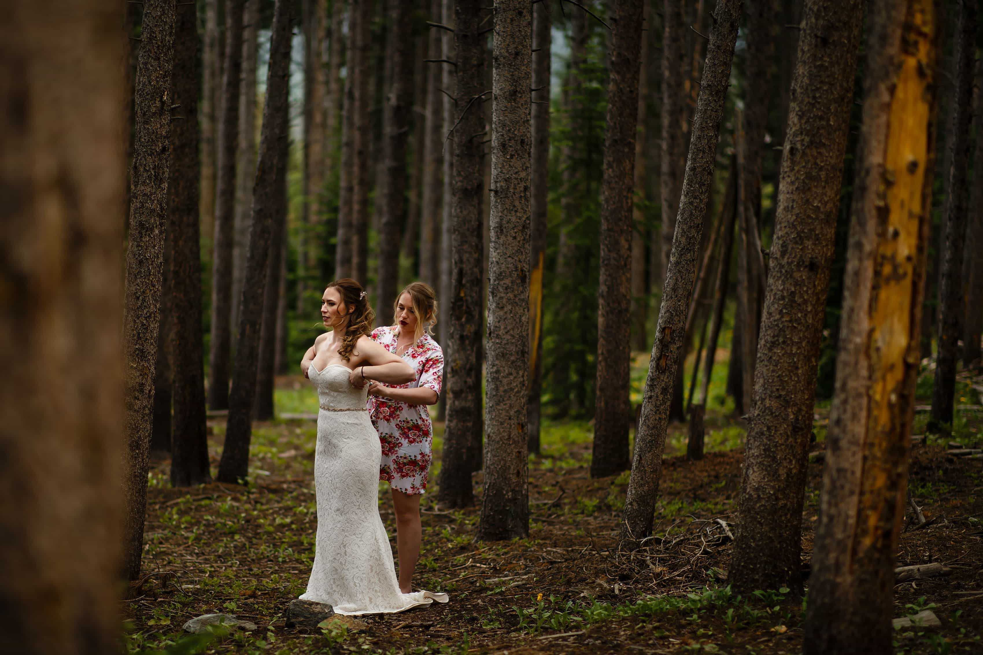 A bride puts on her wedding dress in the woods in Breckenridge