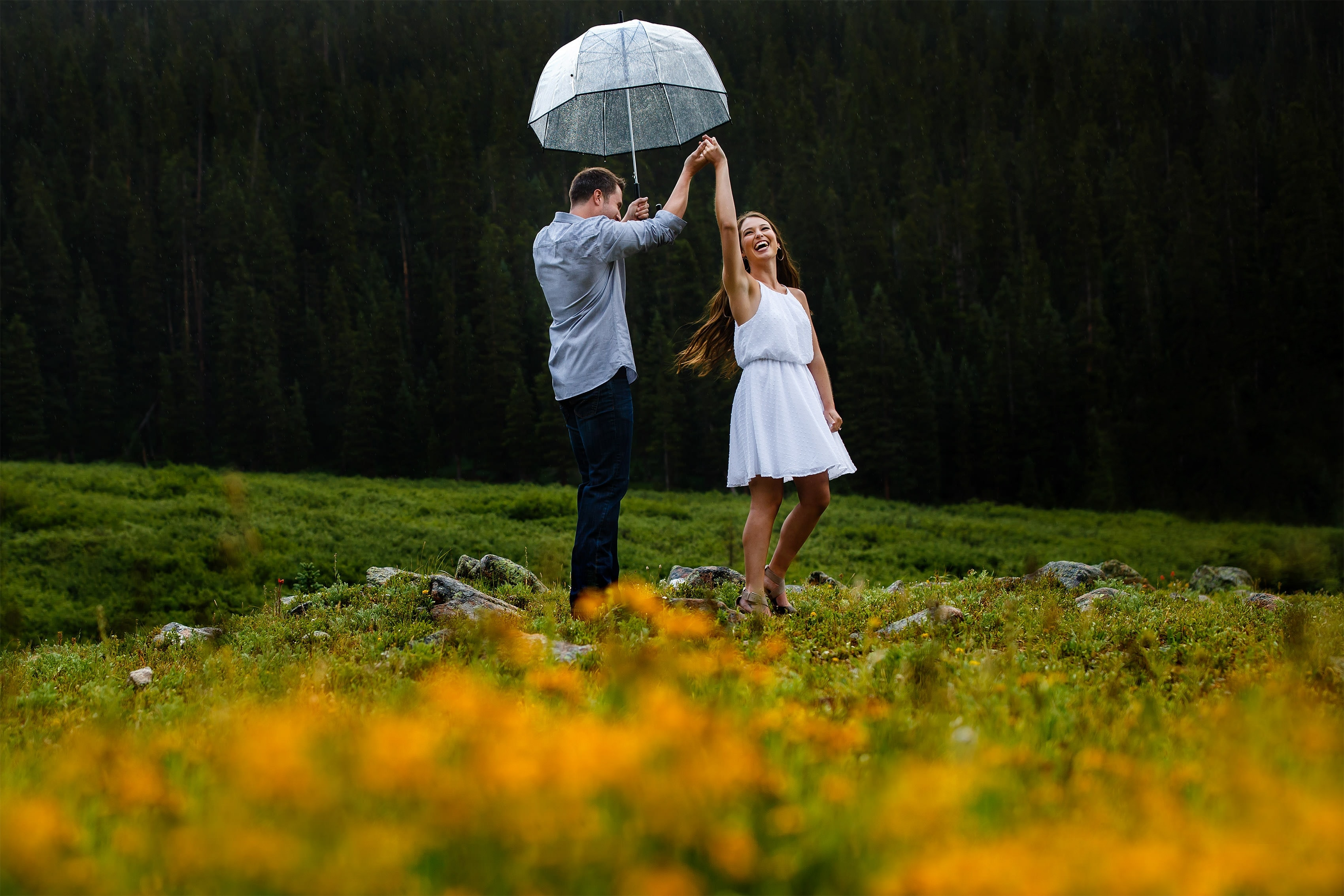 A couple dances in the rain on Loveland Pass near wildflowers