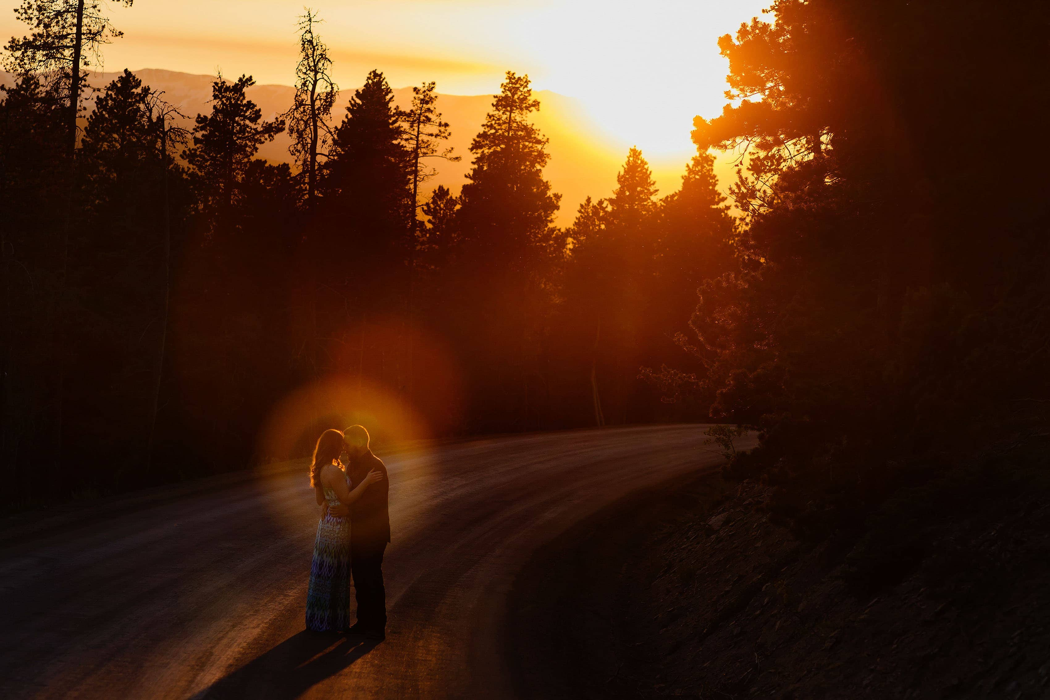 A couple embraces on Gap Road in Golden during their engagement session at sunset