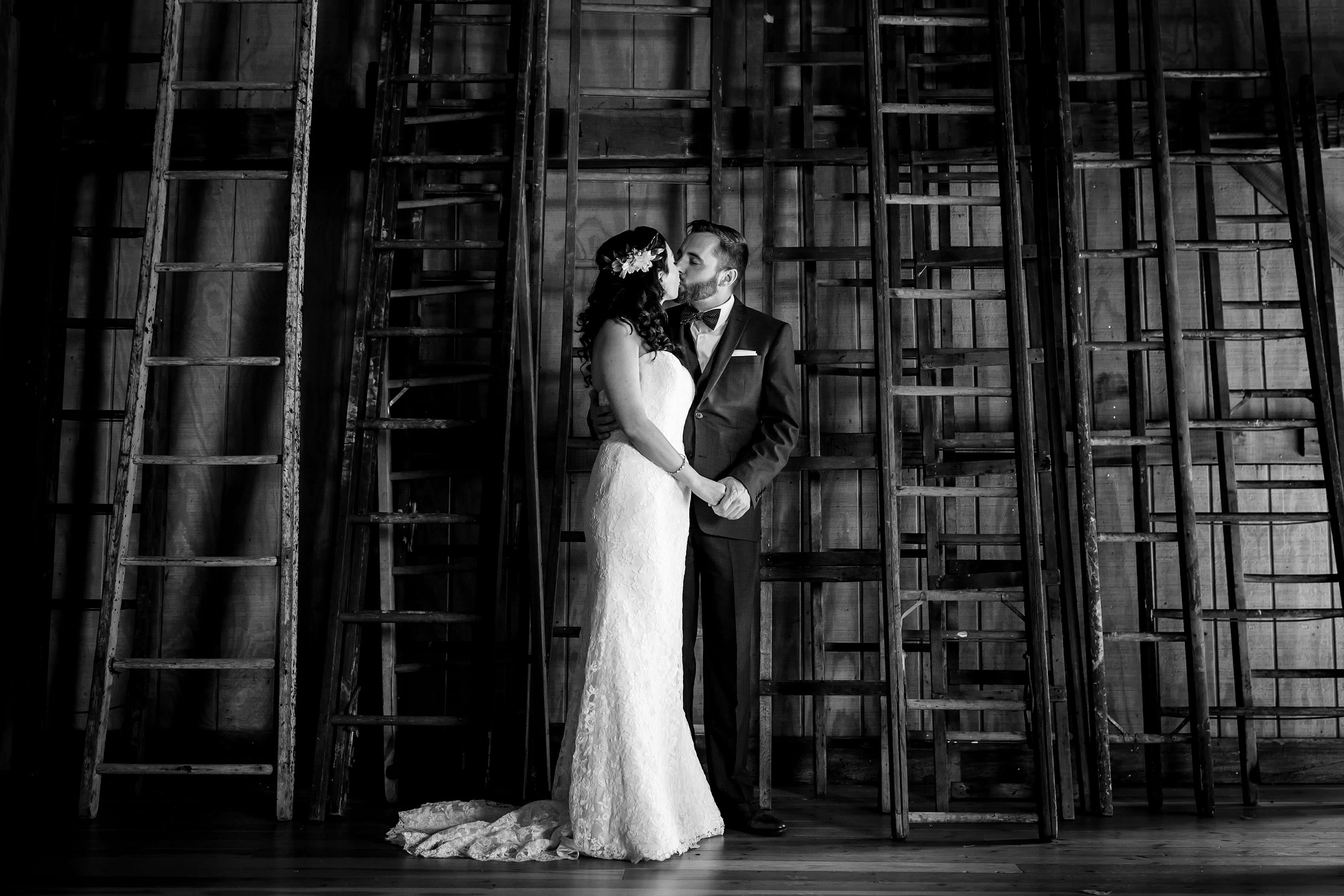 Caitlin and Matt kiss during their first look in a barn in Three Oaks Michigan before their Willow Harbor Vineyards wedding