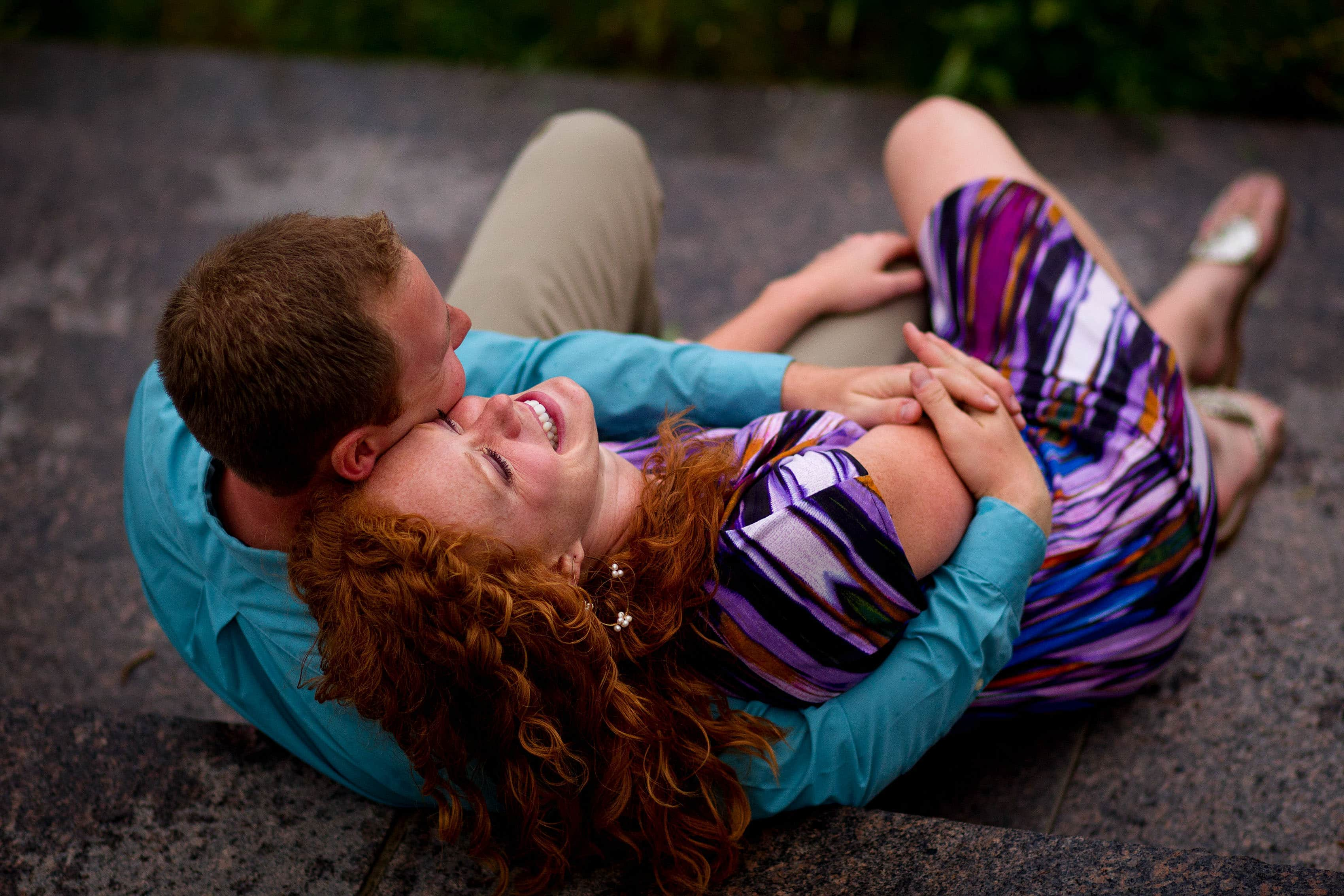 Denver couple snuggle during their engagement at Riverfront Park