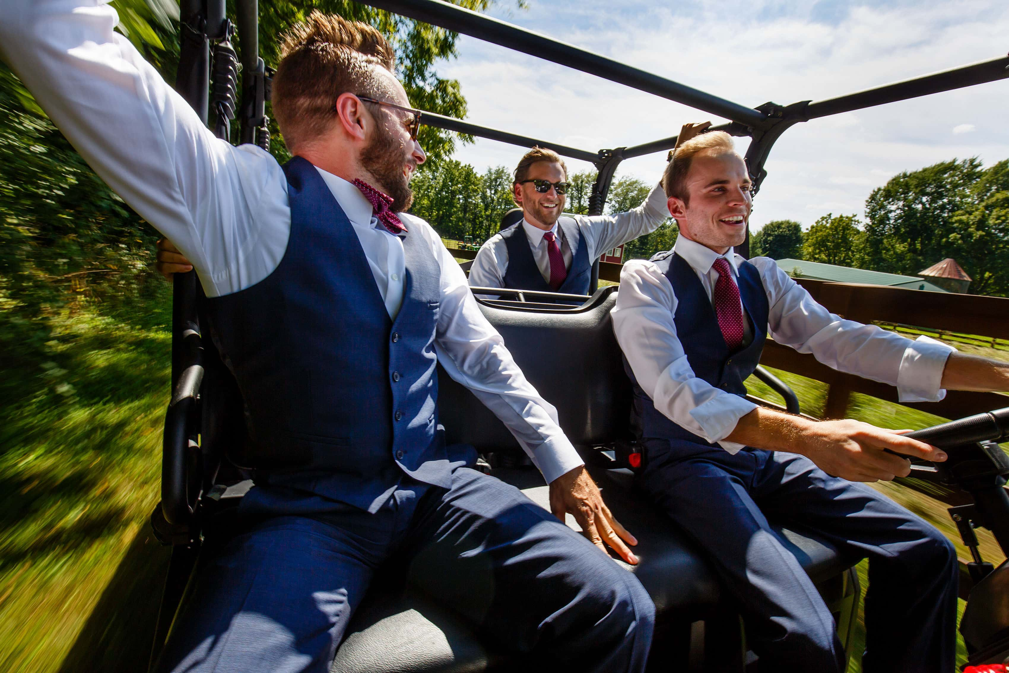 Groomsmen ride in an ATV around a farm near Willow Harbor Vineyards in Three Oaks Michigan