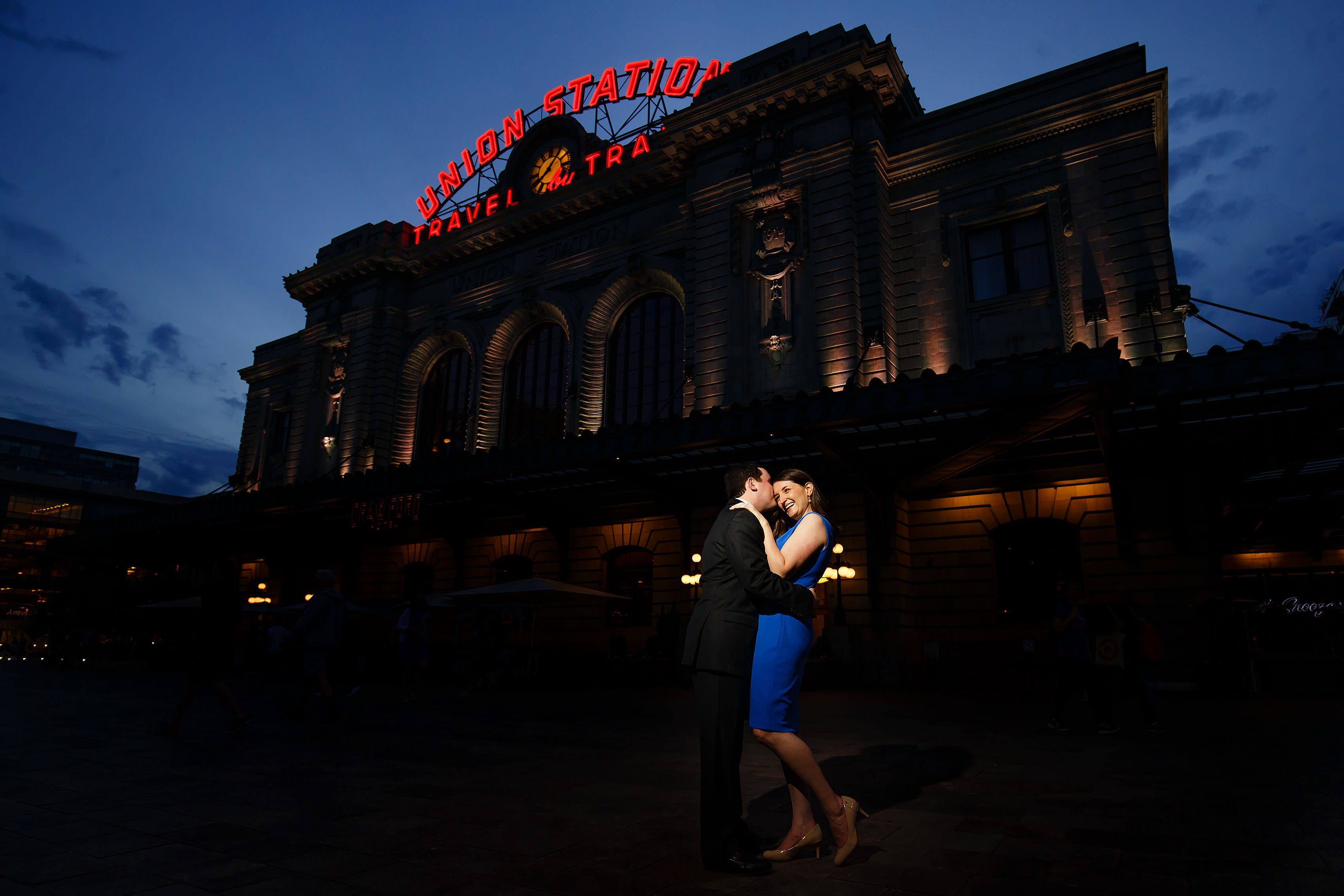 Joel kisses Katie in front of Denver's Union Station during their engagement photos during twilight
