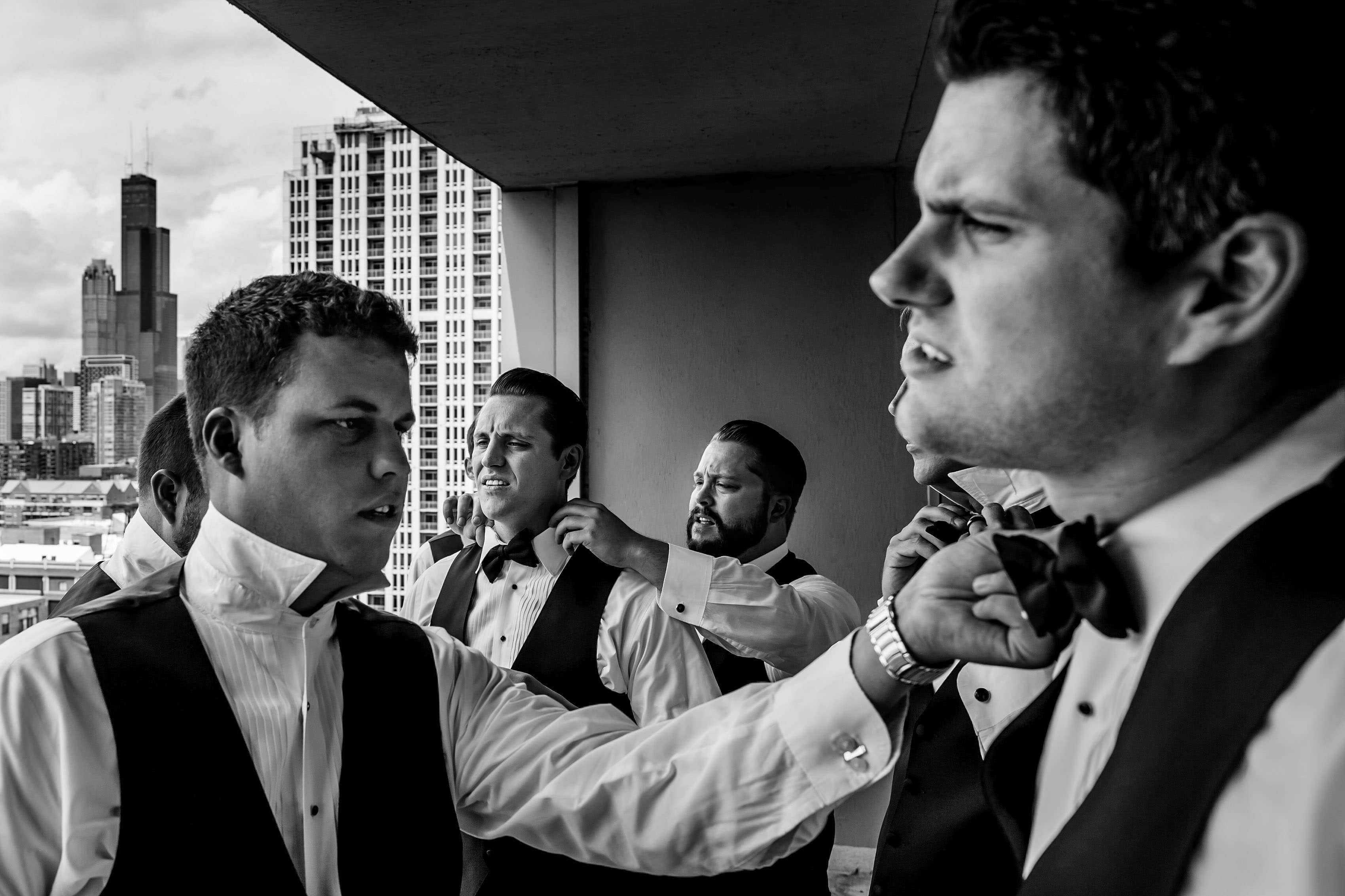 The groom and his groomsmen help adjust each others bowtie near Willis Tower in Chicago