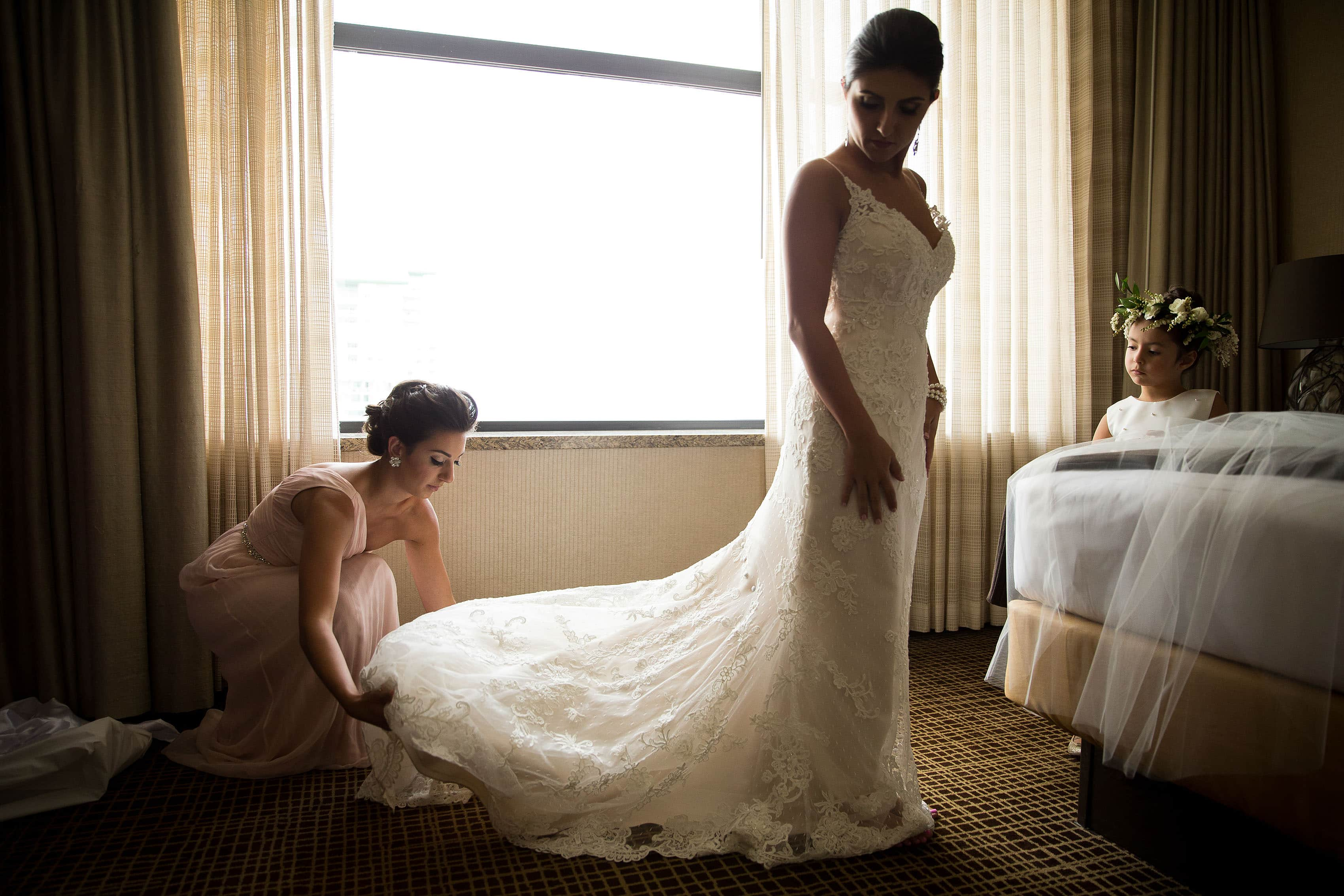 The maid of honor adjusts the brides gown at the Grand Hyatt Denver