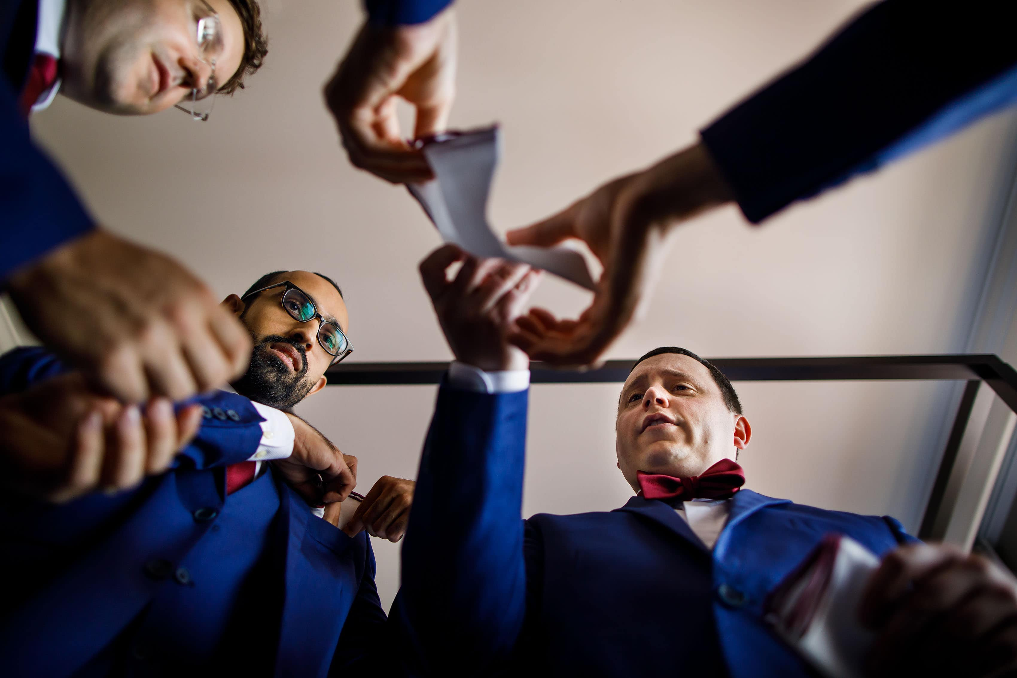 The groom and groomsmen adjust pocket squares at La Banque hotel