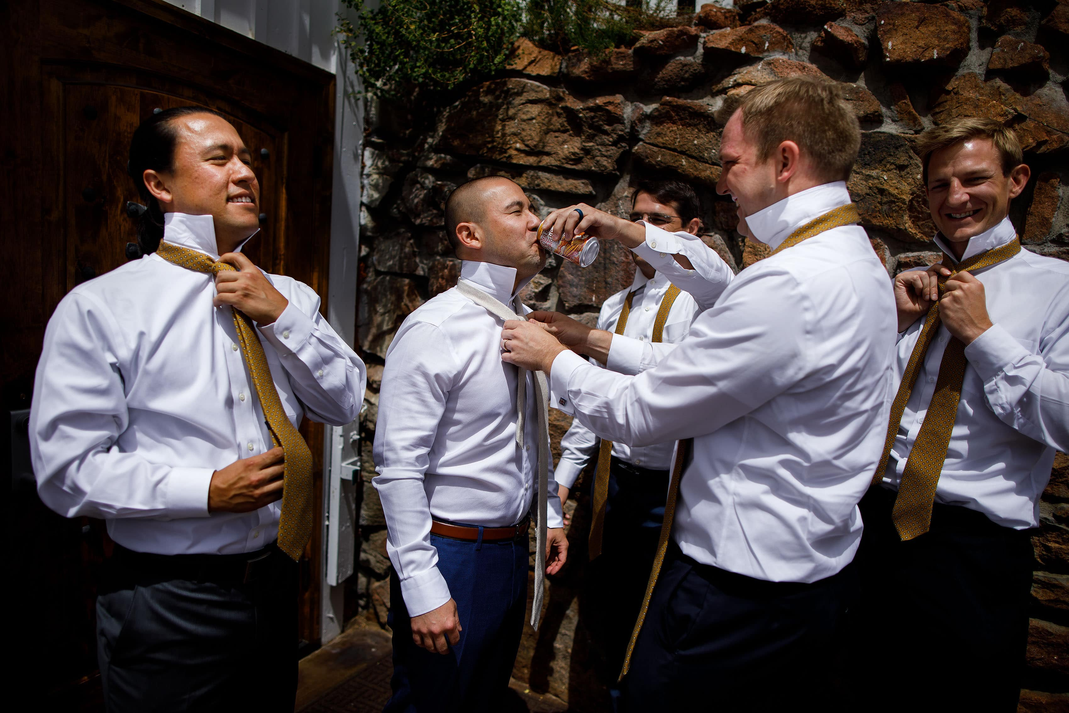 Groomsmen help the groom tie his tie and drink a beer at Deer Creek Valley Ranch