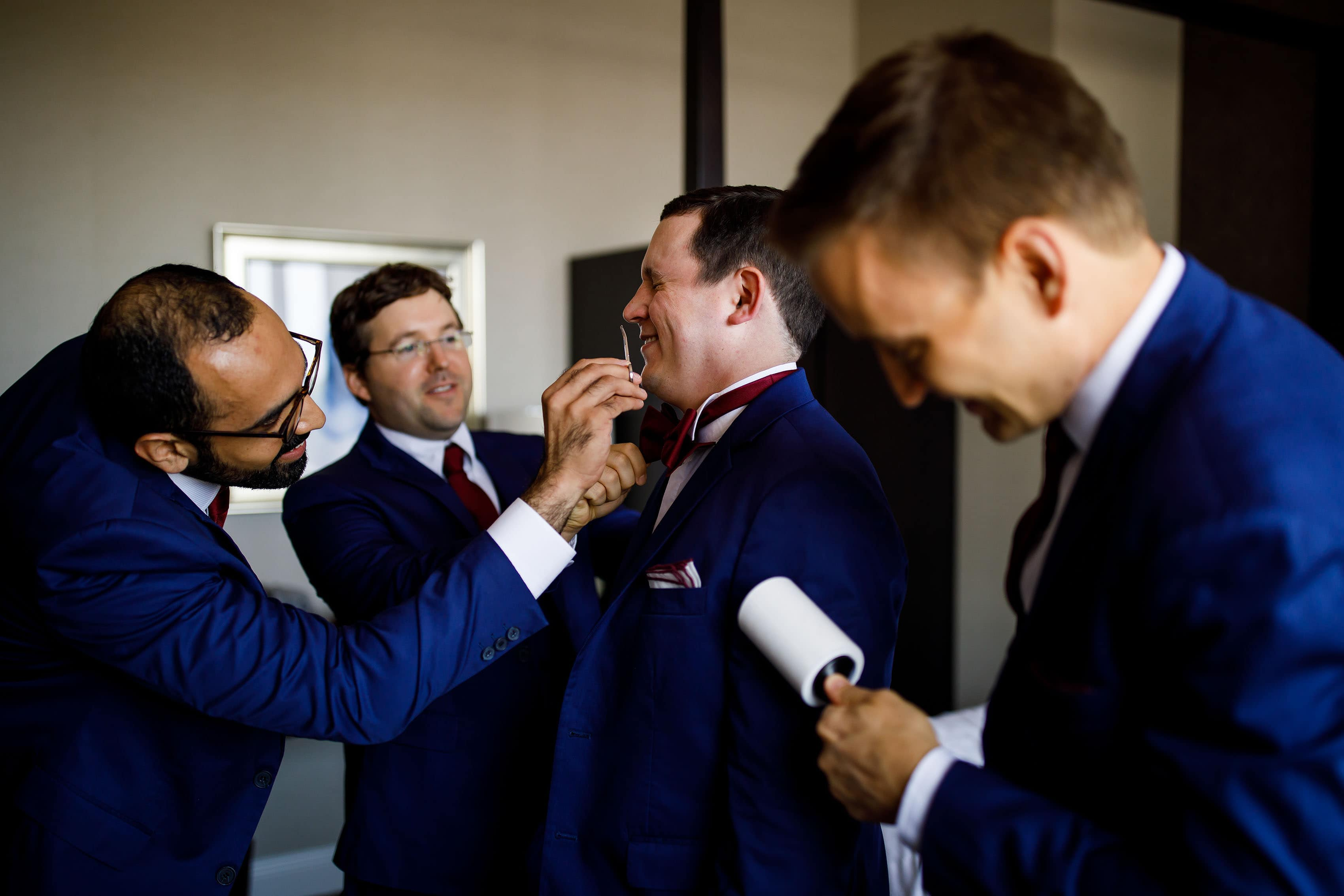 The groom receives some help from his groomsmen while getting ready for the wedding at La Banque hotel