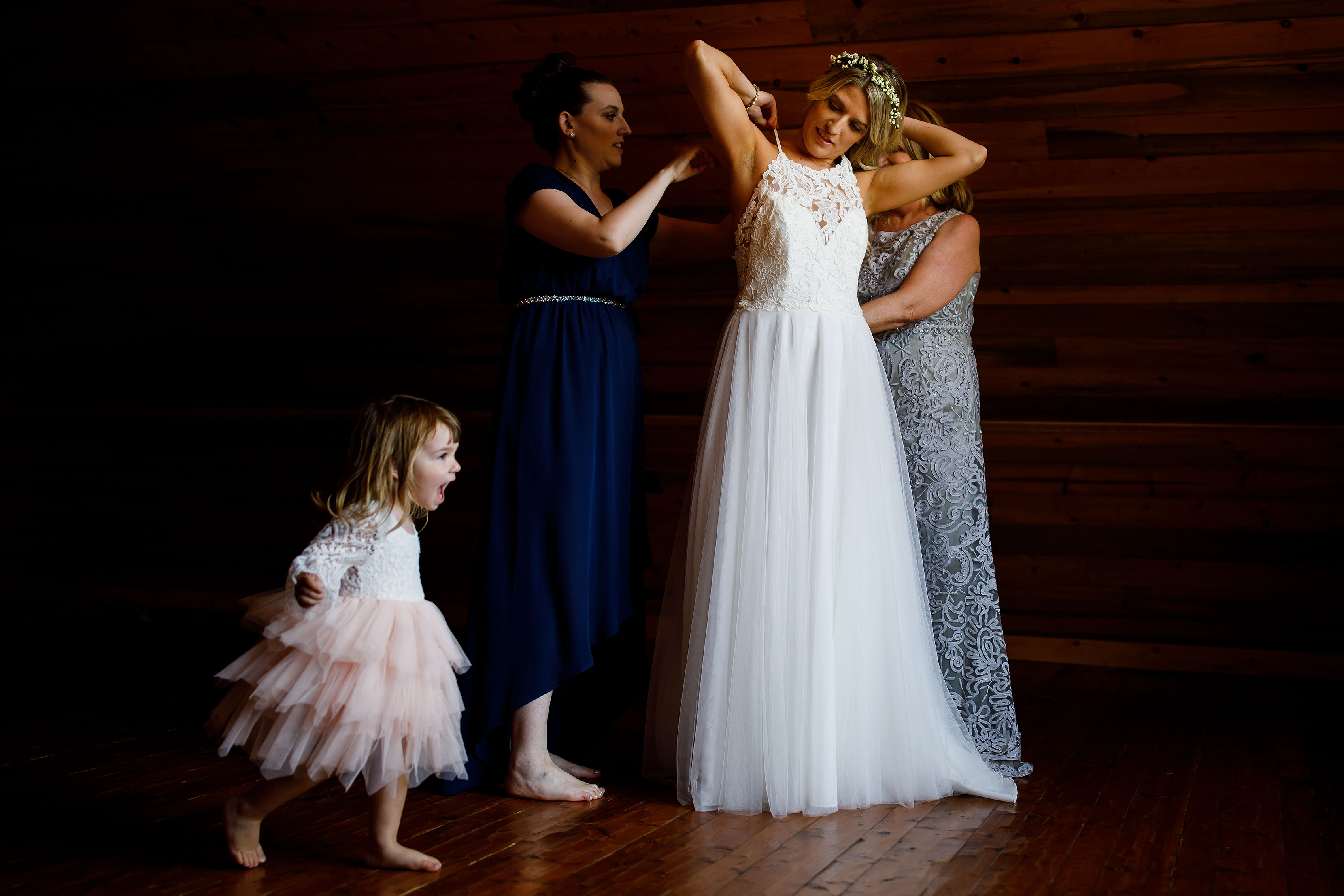 The bride put on her gown as the flower girl runs