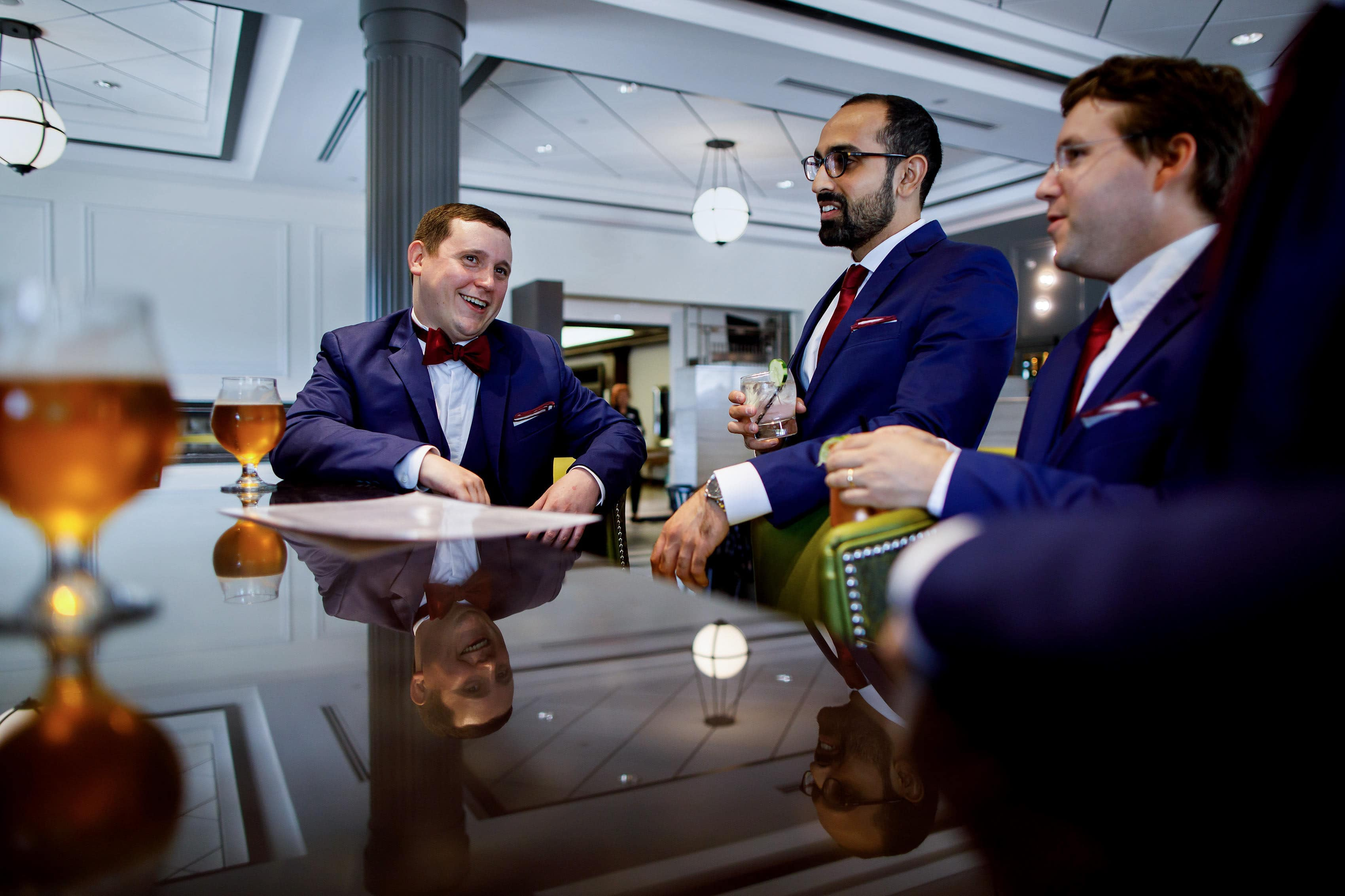 The groom shares a beer with groomsmen at La Banque hotel bar