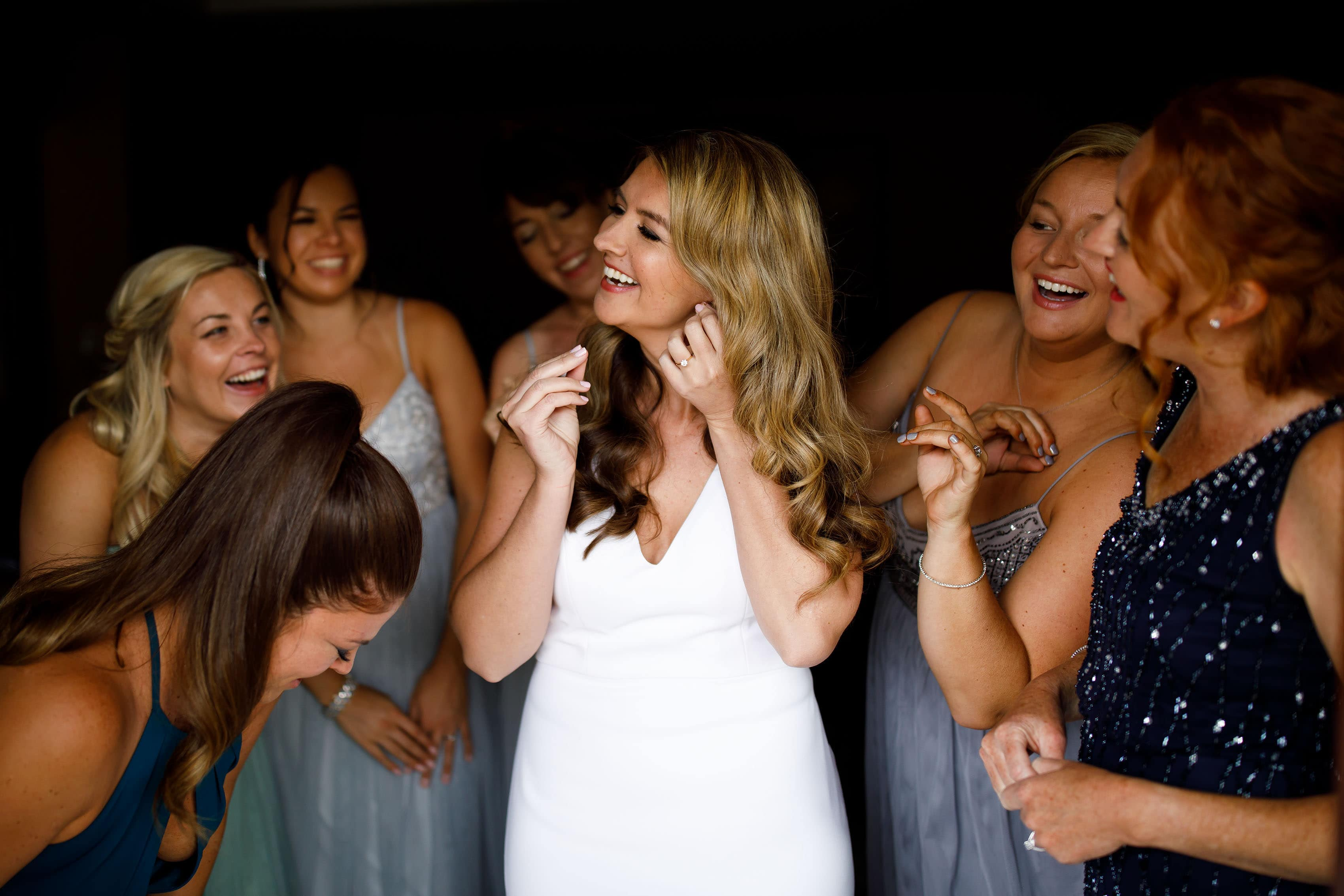 The bride puts on earrings with bridesmaids in Breckenridge