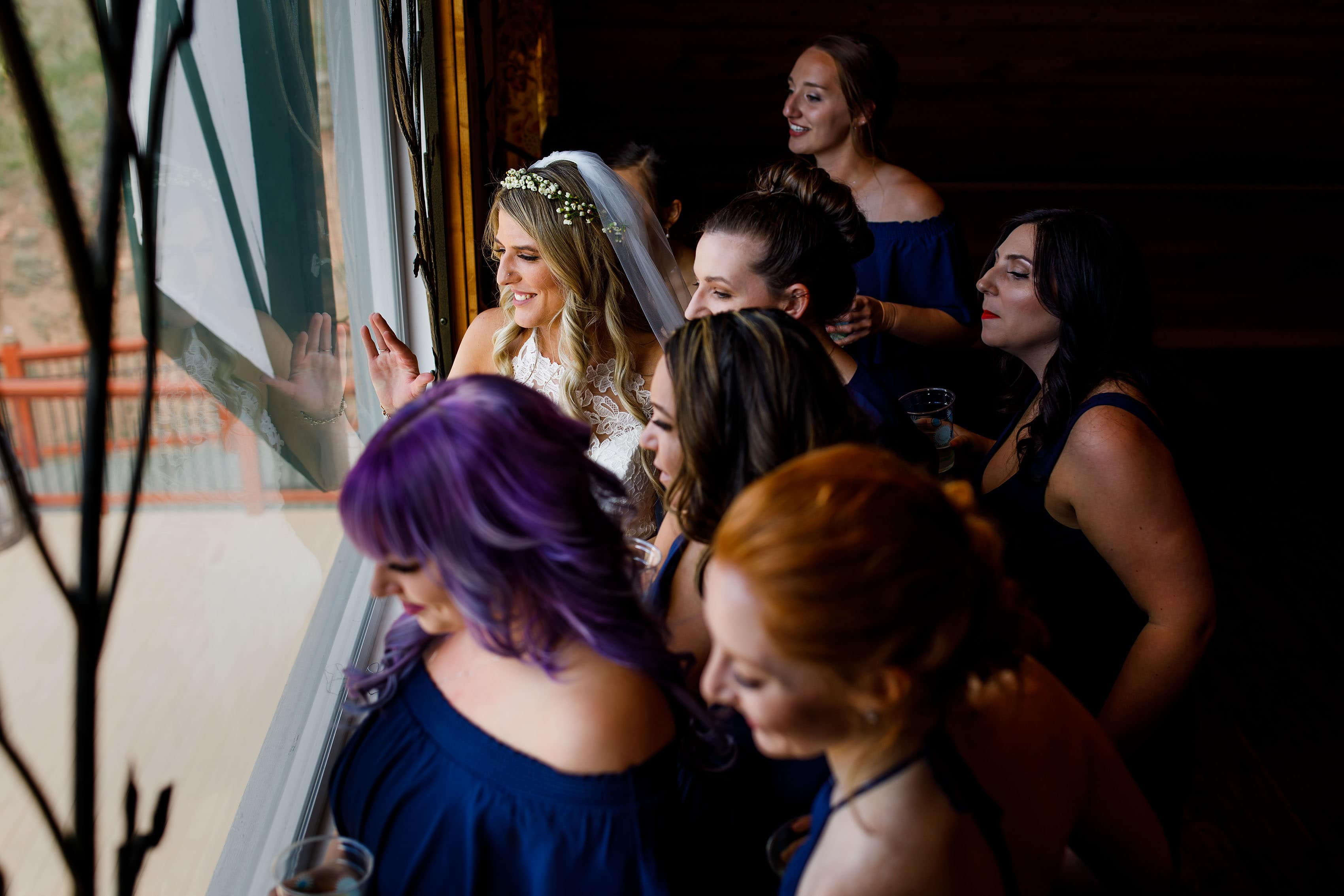 The bridal party wave out the window