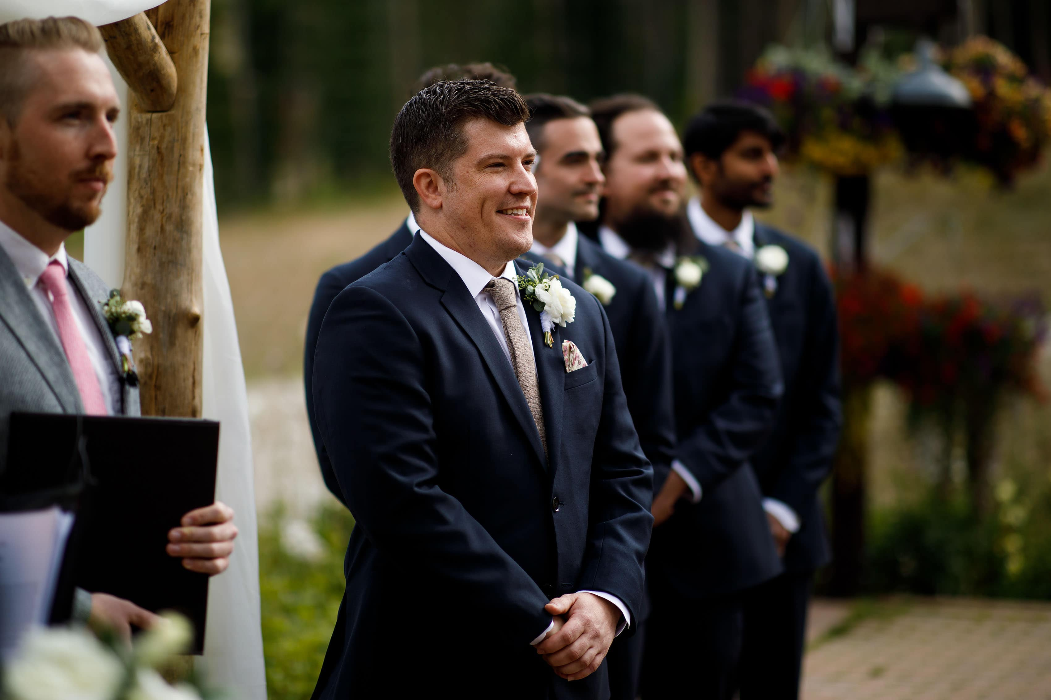 the groom stands during the ceremony