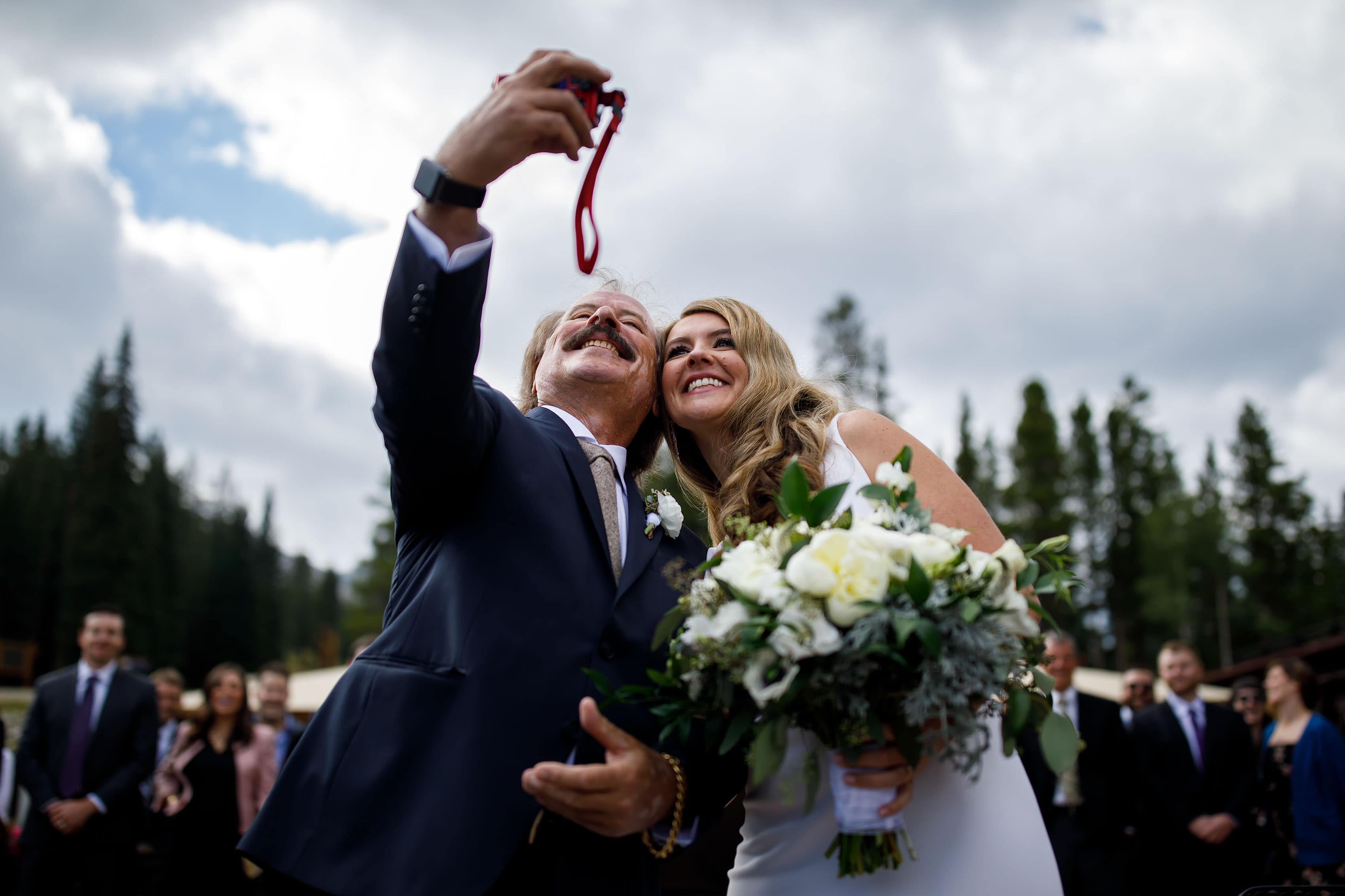 the bride takes a selfie with her father