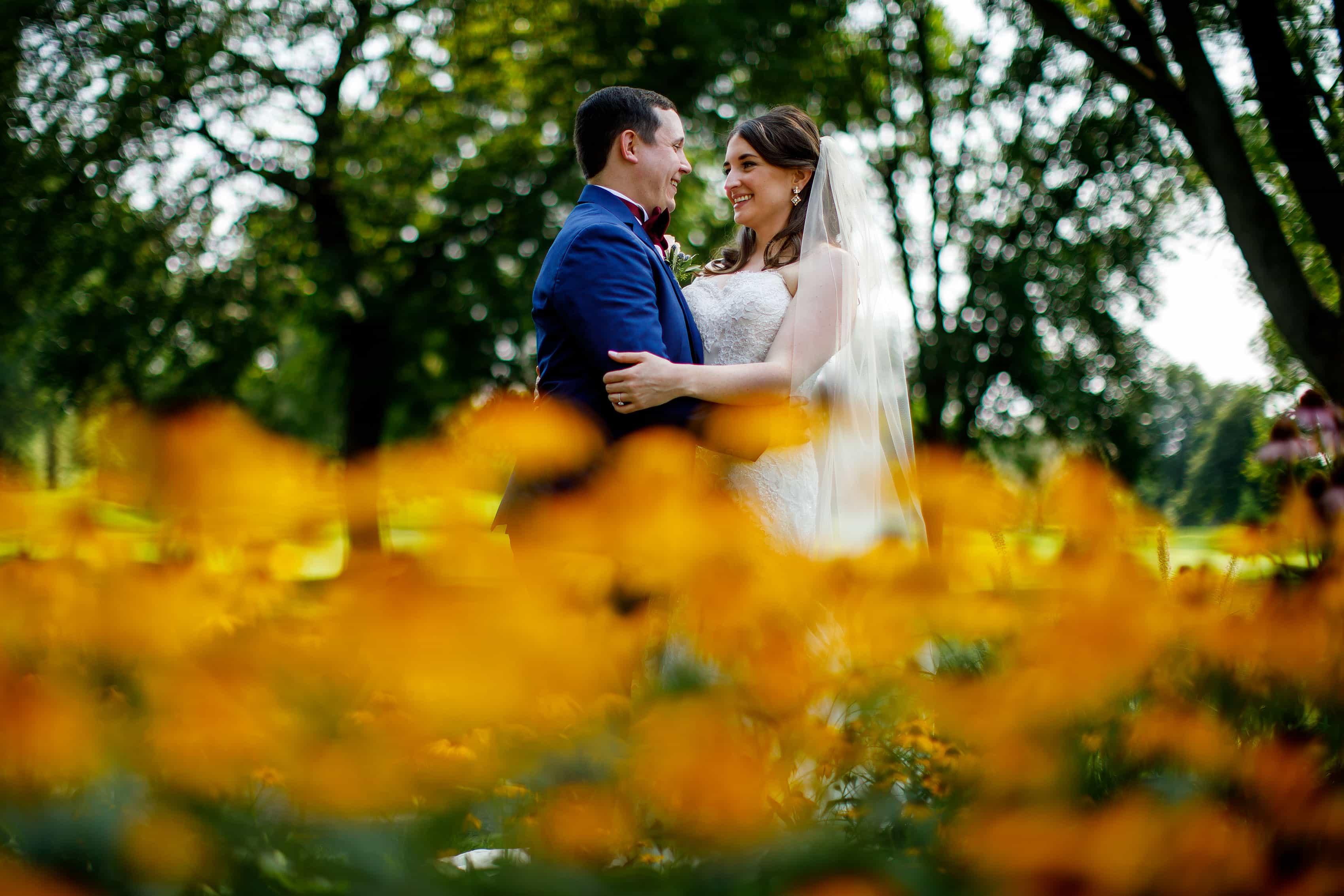 Katie and Joel embrace near the flower garden