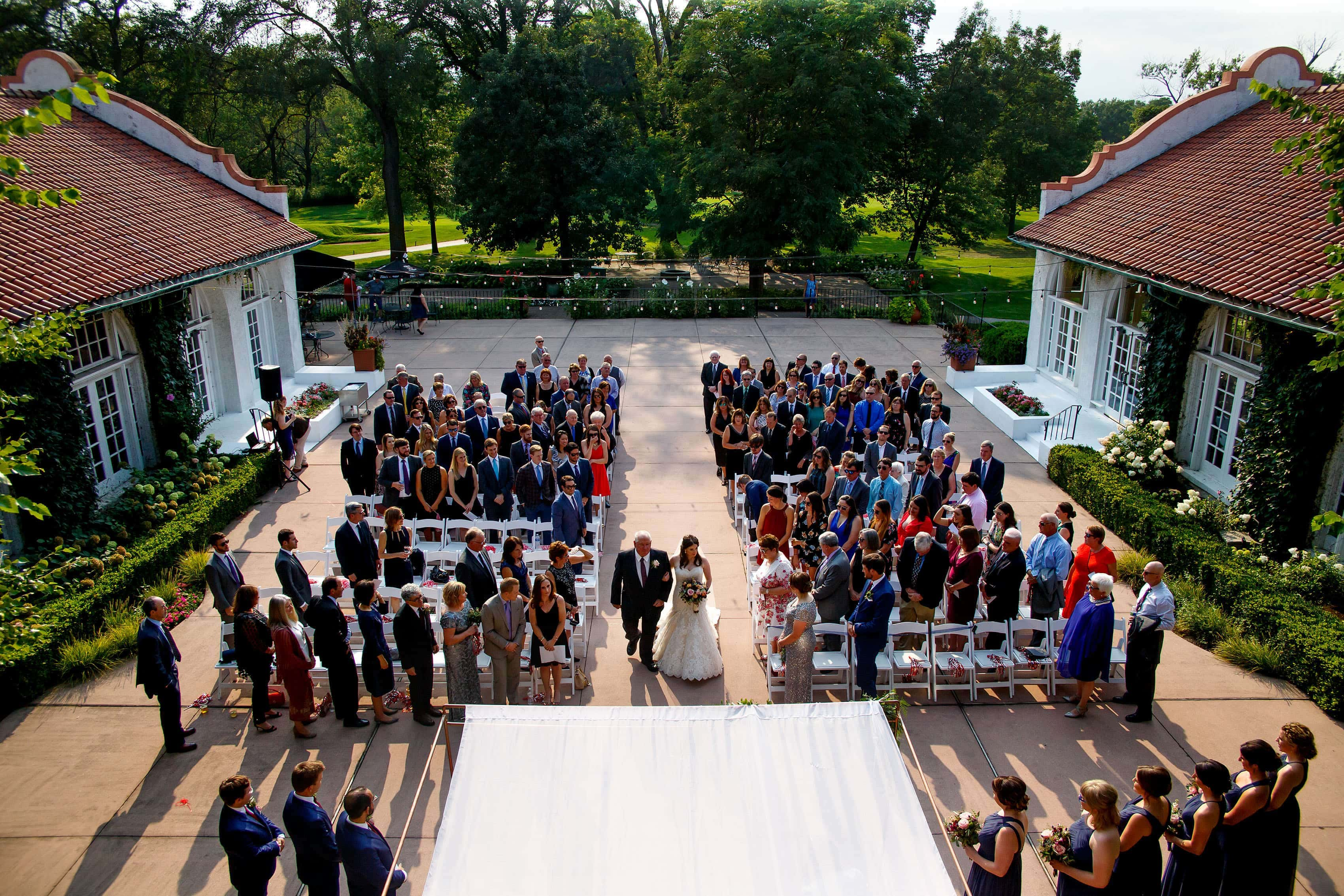 A bride walks down the aisle in the courtyard during her Ravisloe Country Club wedding