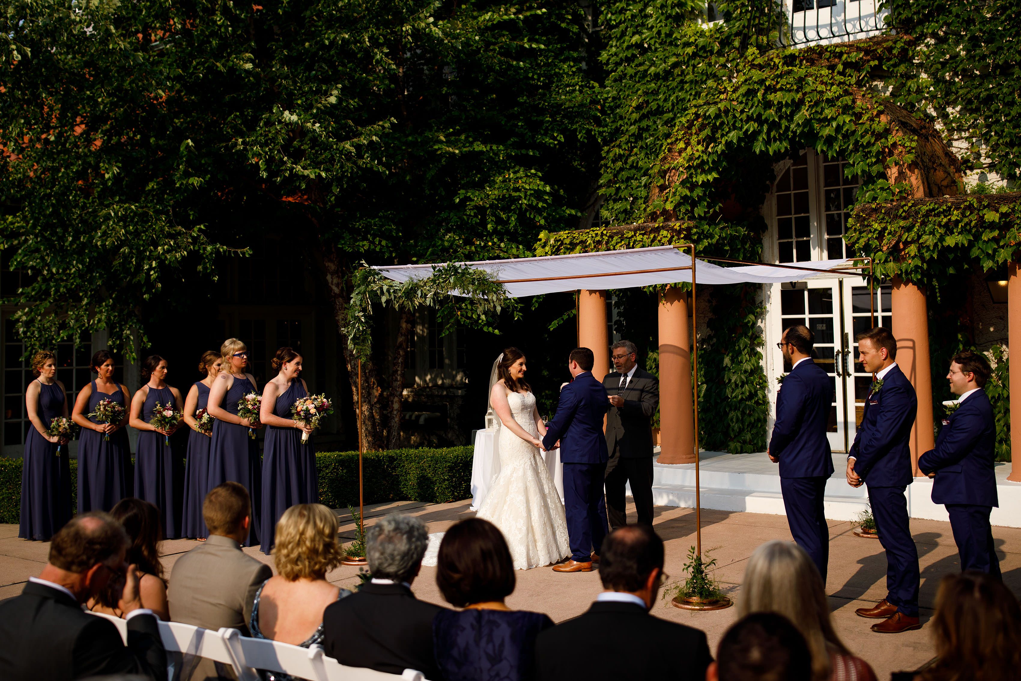 Katie and Joel stand under the chuppah