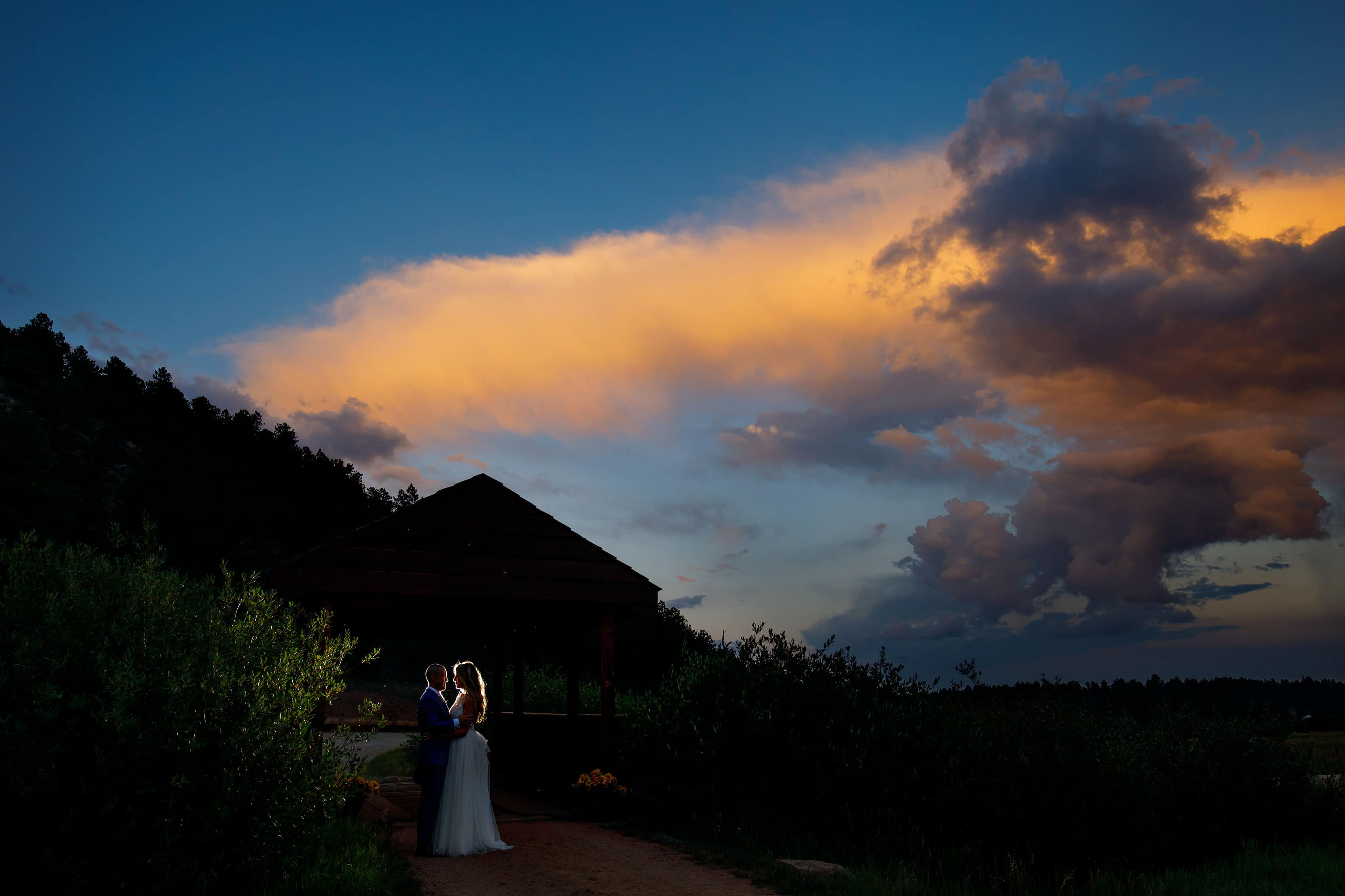 The couple are illuminated on the bridge at sunset during their summer barn wedding at Deer Creek Valley Ranch