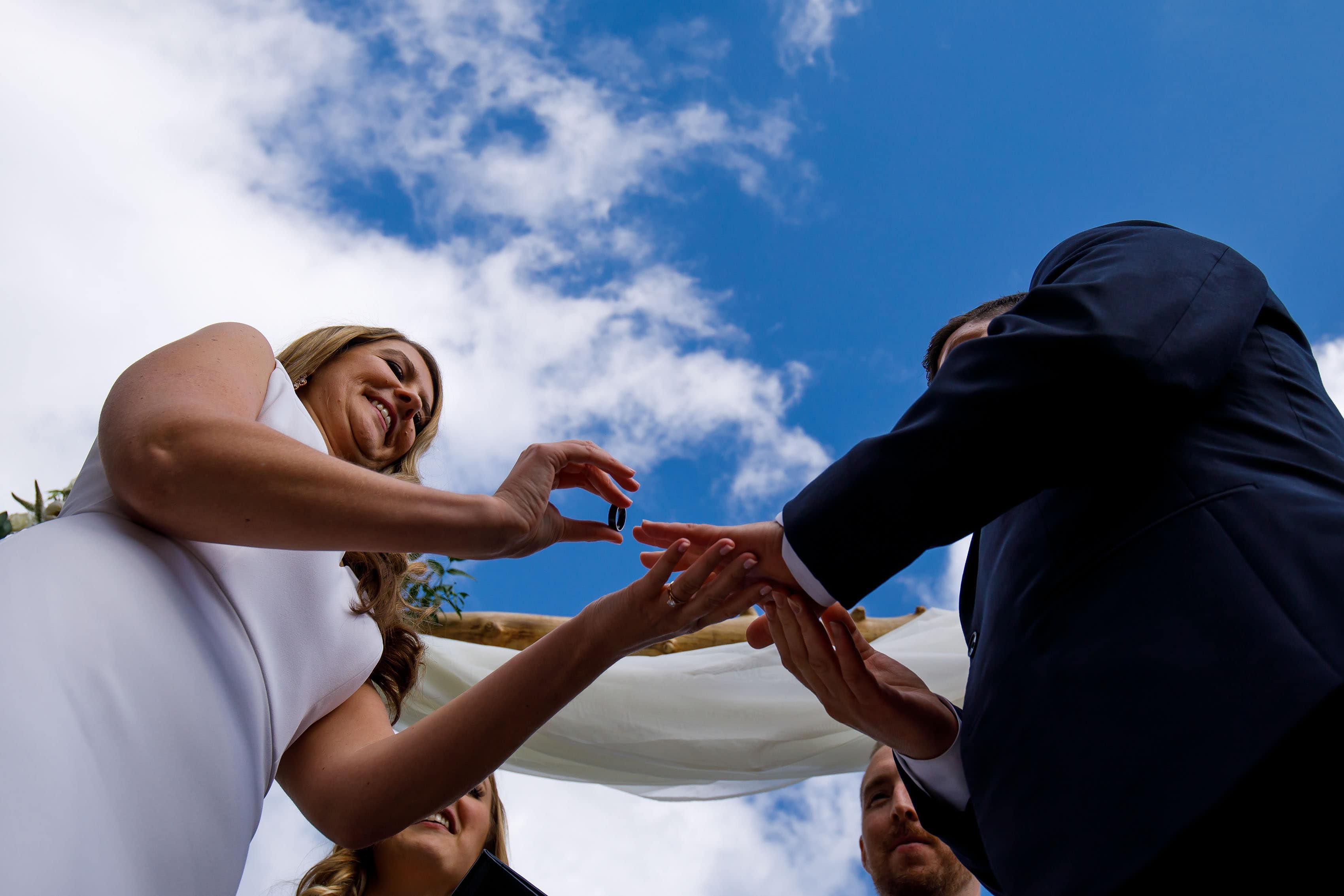 The bride puts a wedding ring on the grooms finger