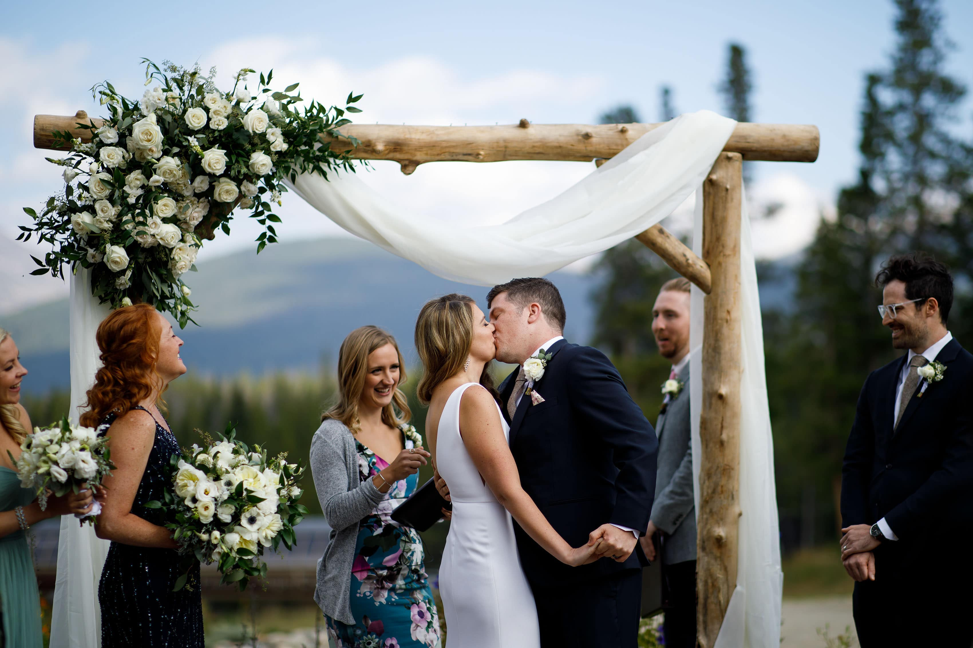 The couple share a first kiss under a wood arch at TenMile