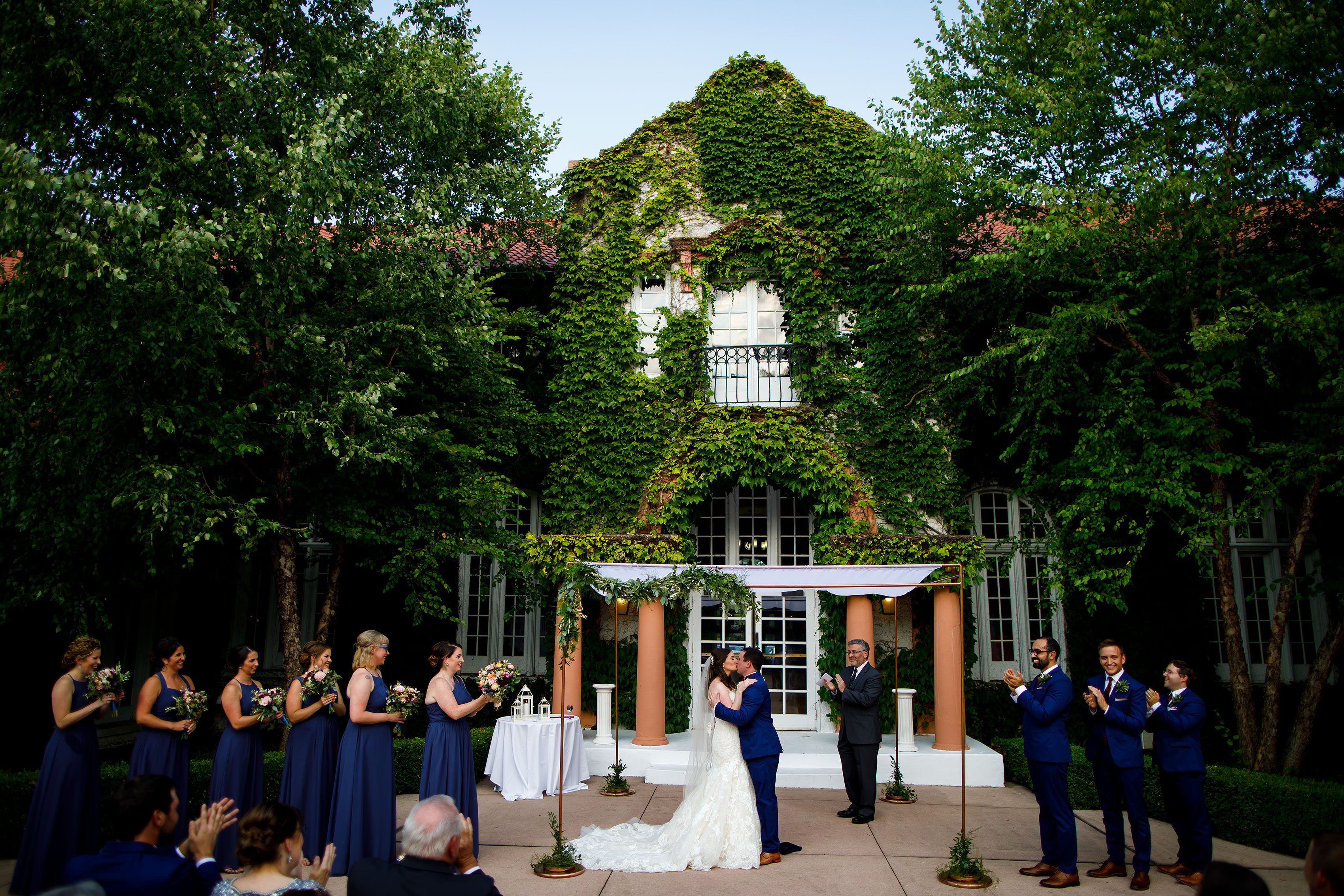 A bride and groom share their first kiss during their Ravisloe Country Club wedding