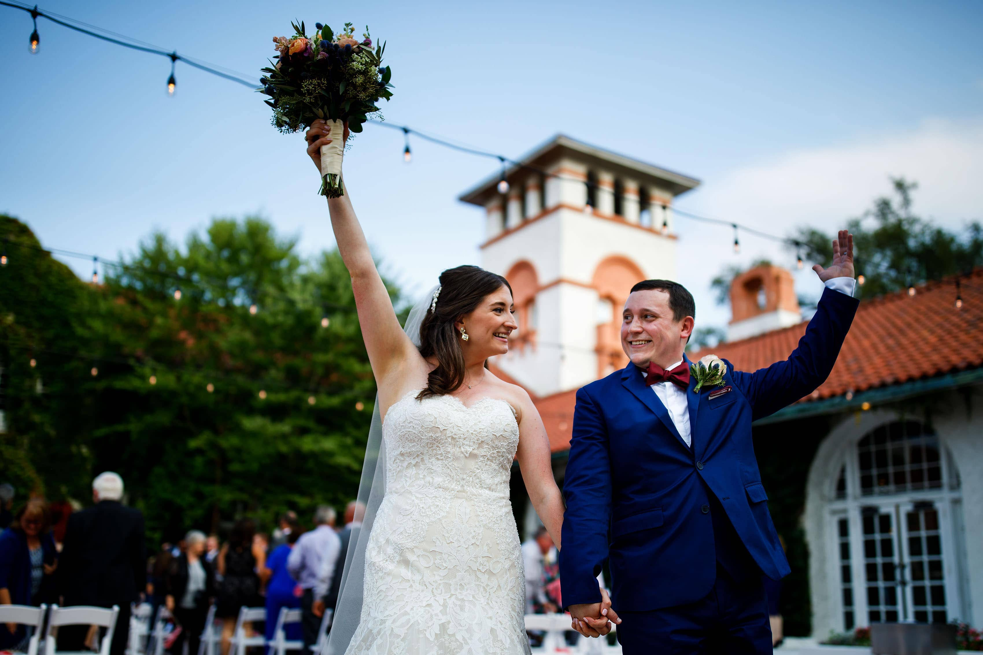 The bride and groom celebrate after their Ravisloe Country Club wedding ceremony in the summer in Homewood Illinois