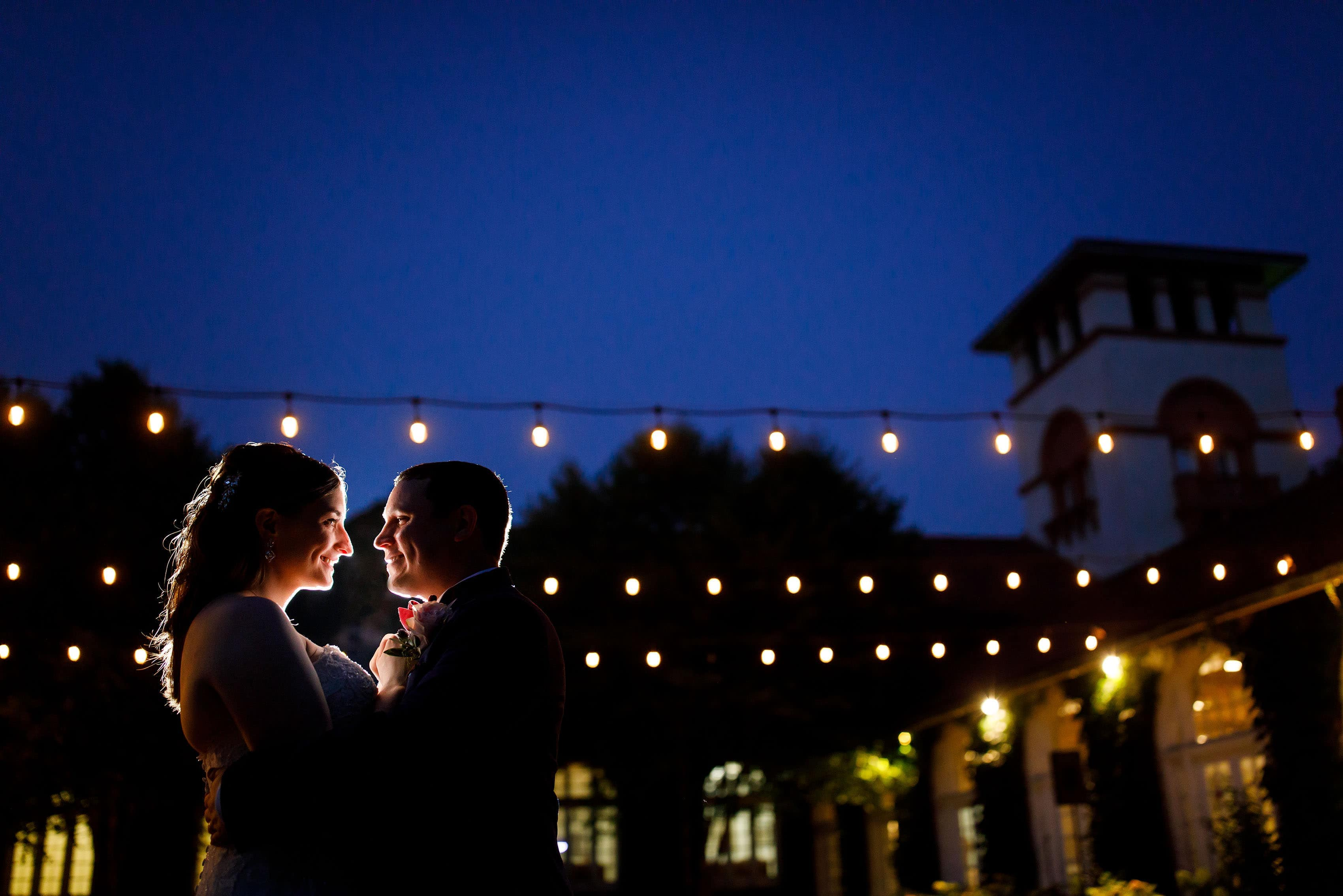 The bride and groom pose for a twilight portrait during their Ravisloe Country Club wedding
