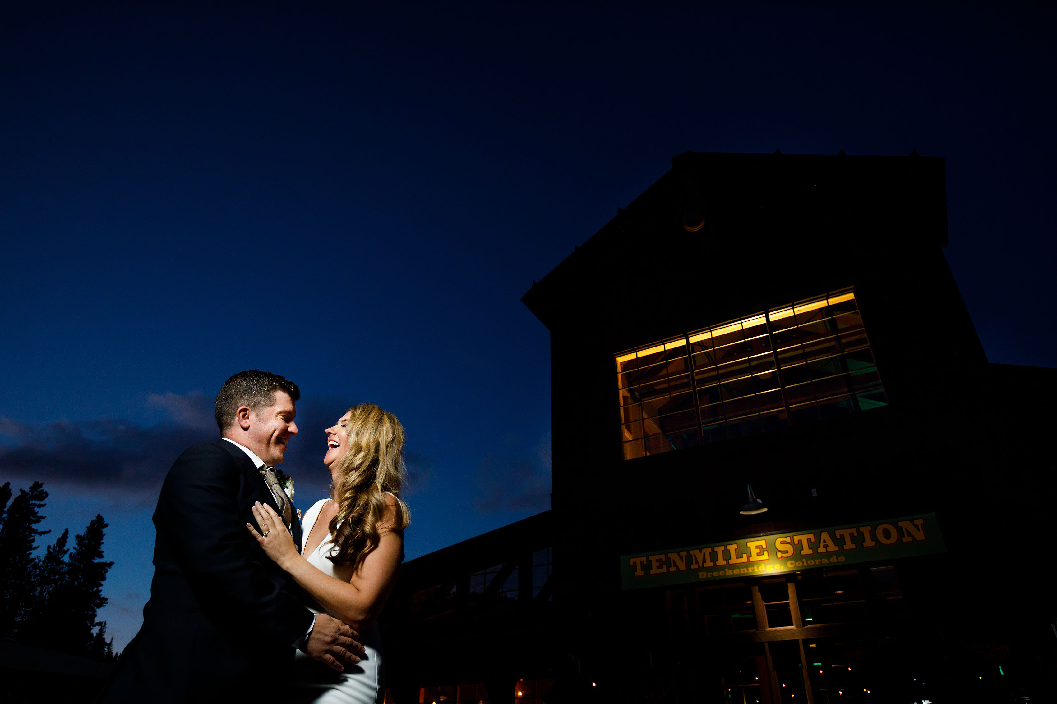 The bride and groom laugh during a portrait at twilight outside their wedding at TenMile Station at Breckenridge