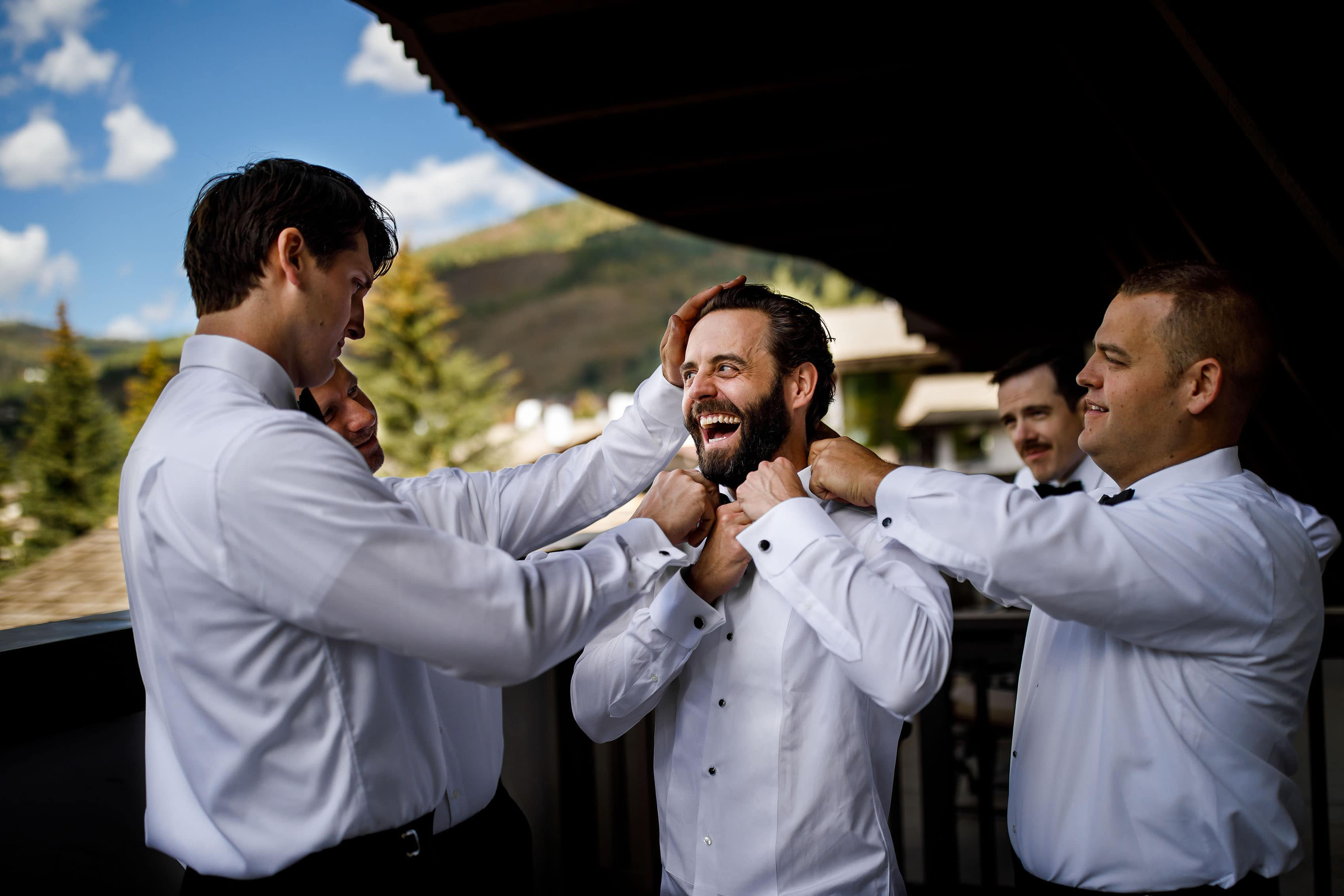 The groom laughs while getting ready for his wedding at the lodge at vail