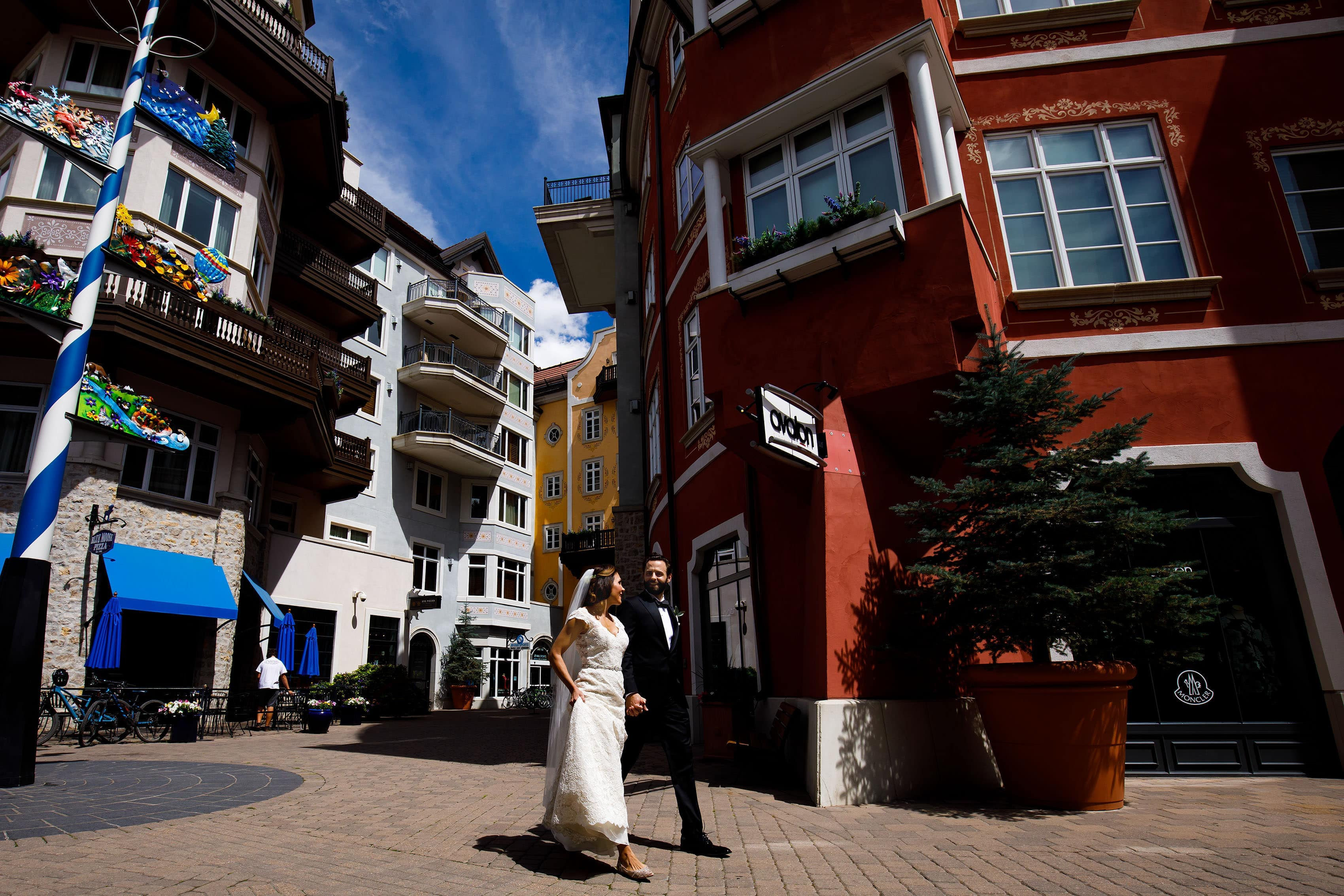 The bride and groom walk through Lionhead village before their Vail wedding